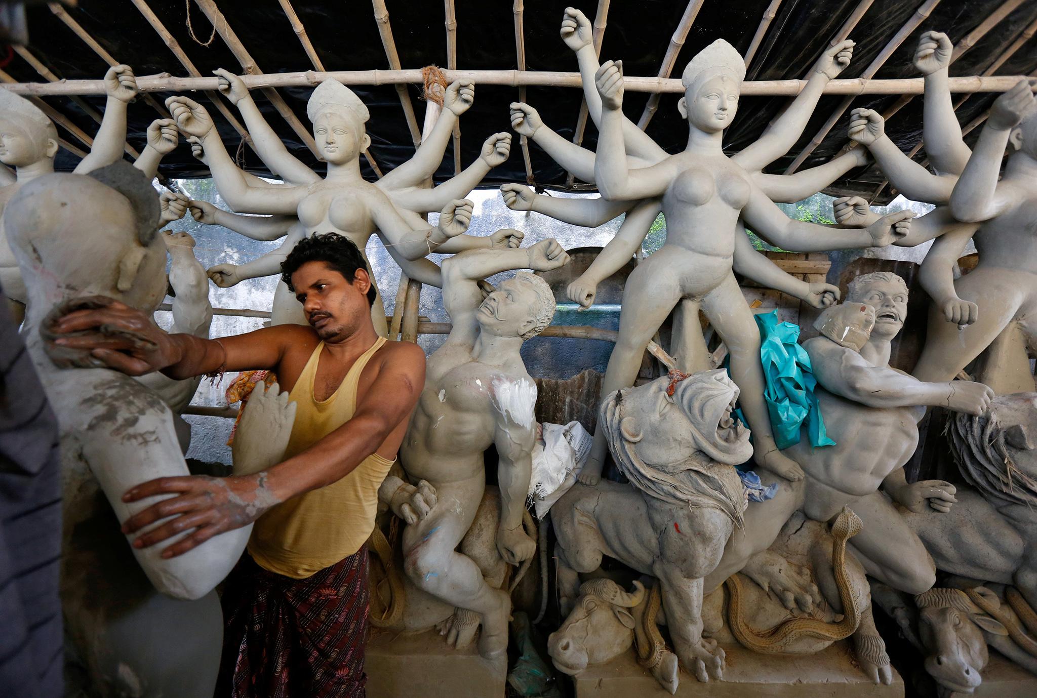 An artisan works on an idol of Hindu goddess Durga at a workshop ahead of the Durga Puja festival in Kolkata, India