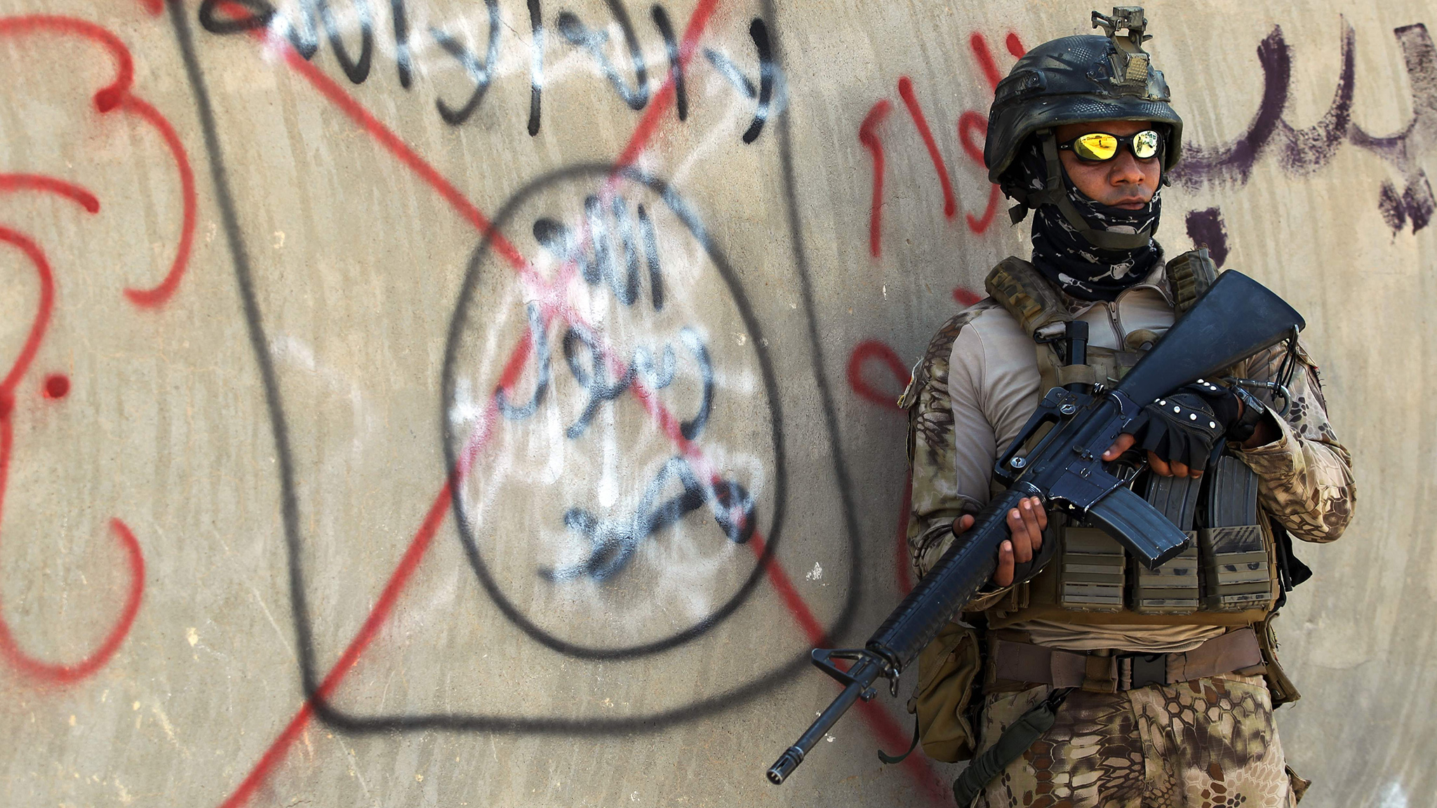 An Iraqi soldier stands next to a wall with a red cross above a slogan of the Islamic State (IS) group, on September 4, 2016 in the city of Fallujah.