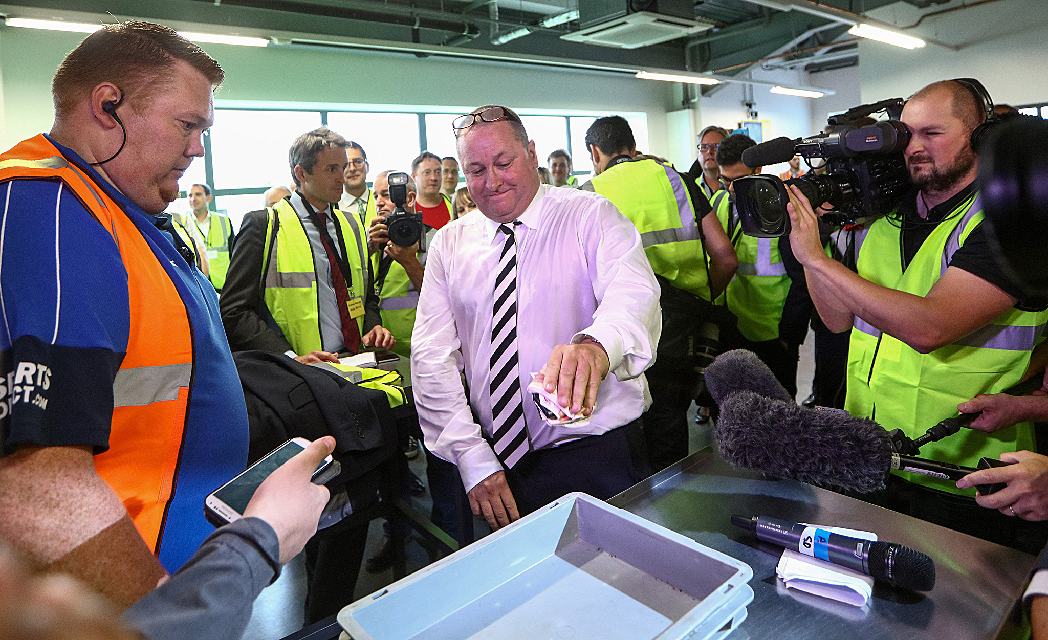 "Mike Ashley, billionaire and founder of Sports Direct International Plc, places his wallet and a wad of 50 pound banknotes as he demonstrates the security checking procedures during a tour of the company's warehouse following the company's annual general meeting (AGM) at their headquarters in Shirebrook, U.K., on Wednesday, Sept. 7, 2016. Britain's biggest sporting-goods retailer has been admonished by lawmakers for presiding over ""appalling"" treatment of workers at its main warehouse and come under fire from shareholders over corporate governance. Photographer: Chris Ratcliffe/Bloomberg"