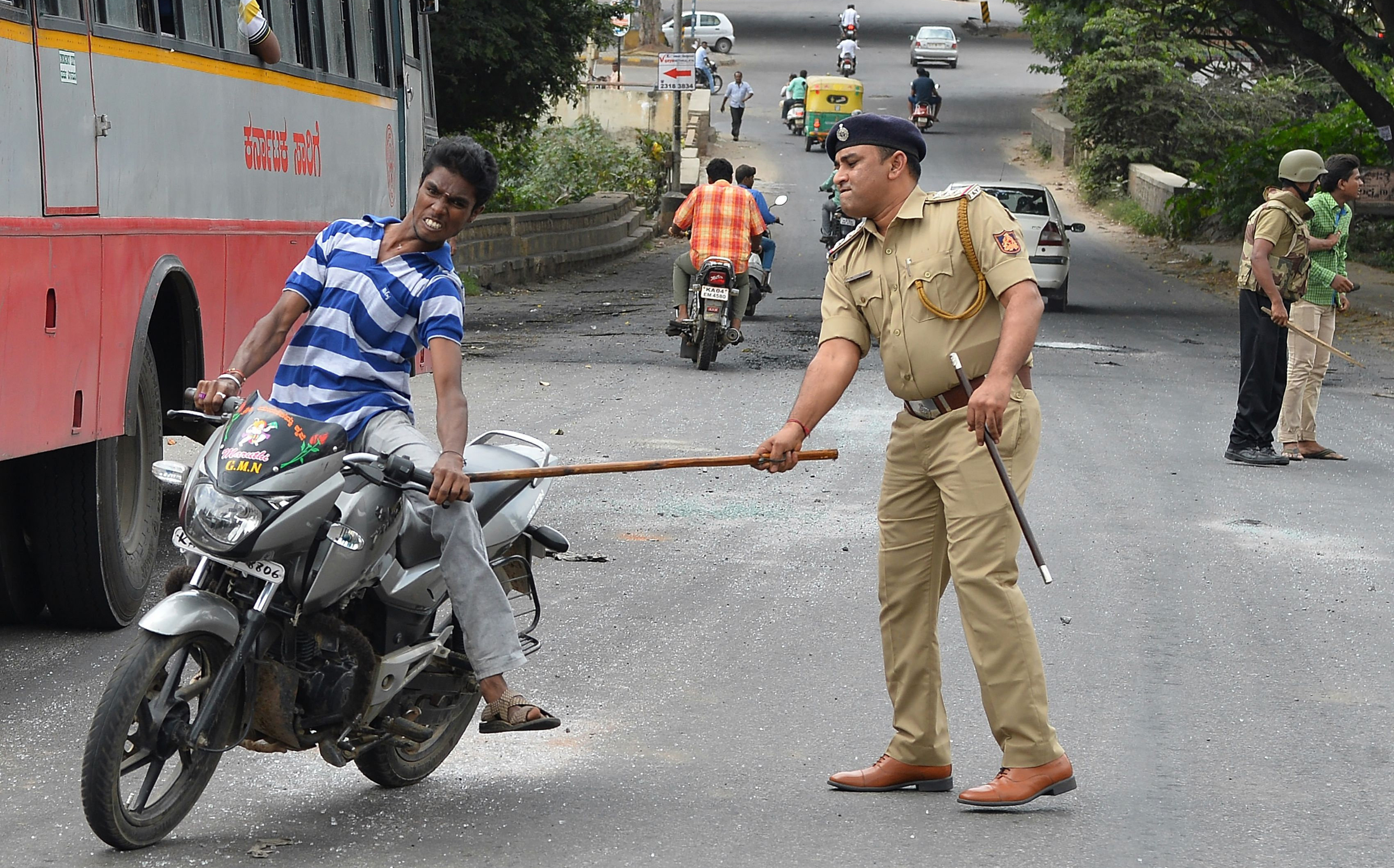 A police personnel canes a motorcyclist during a curfew following violence in the city due to the Cauvery water sharing dispute with neighbouring state Tamil Nadu, in Bangalore