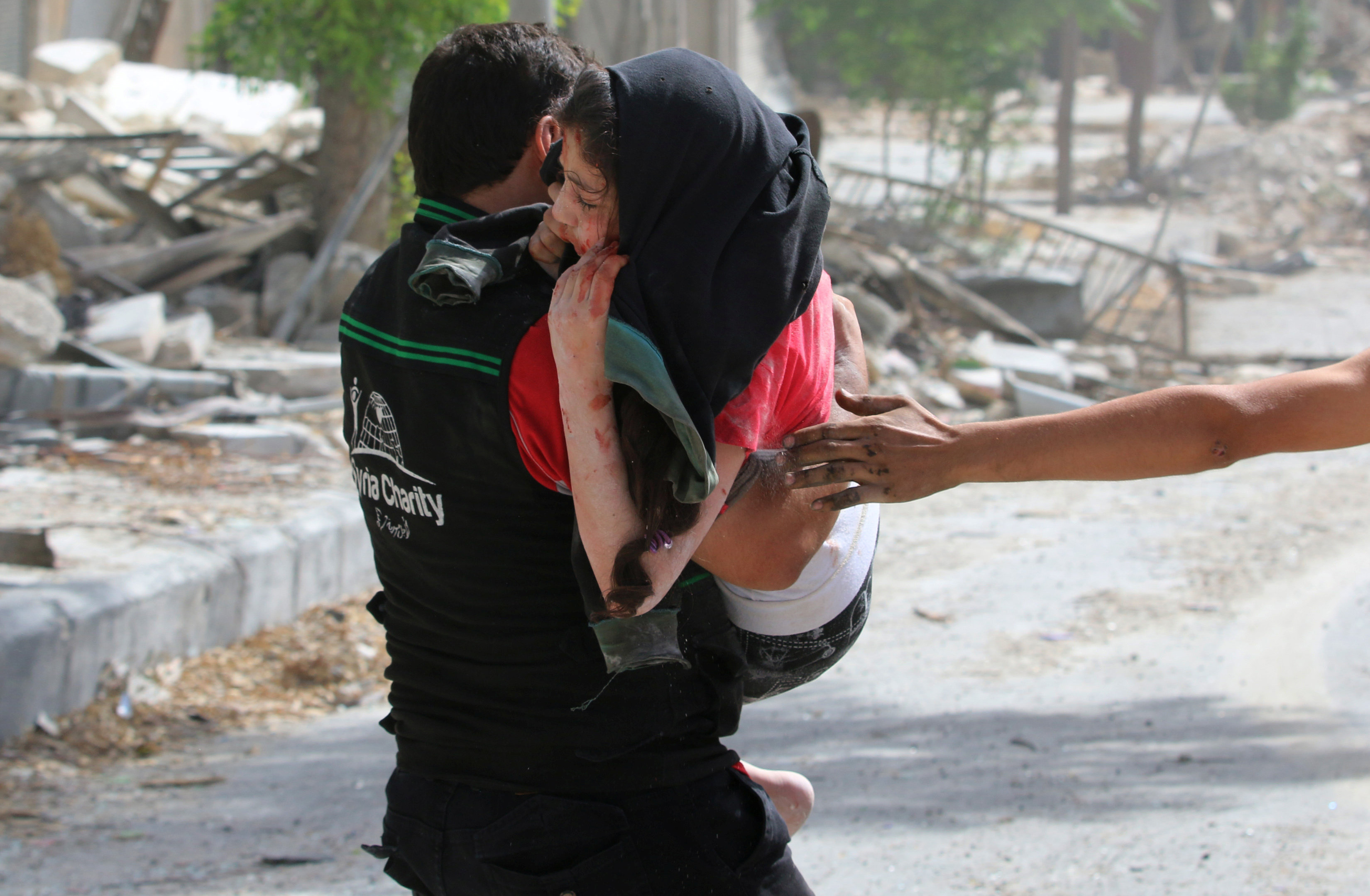 A man carries an injured girl after airstrikes on the rebel held al-Qaterji neighbourhood of Aleppo, Syria