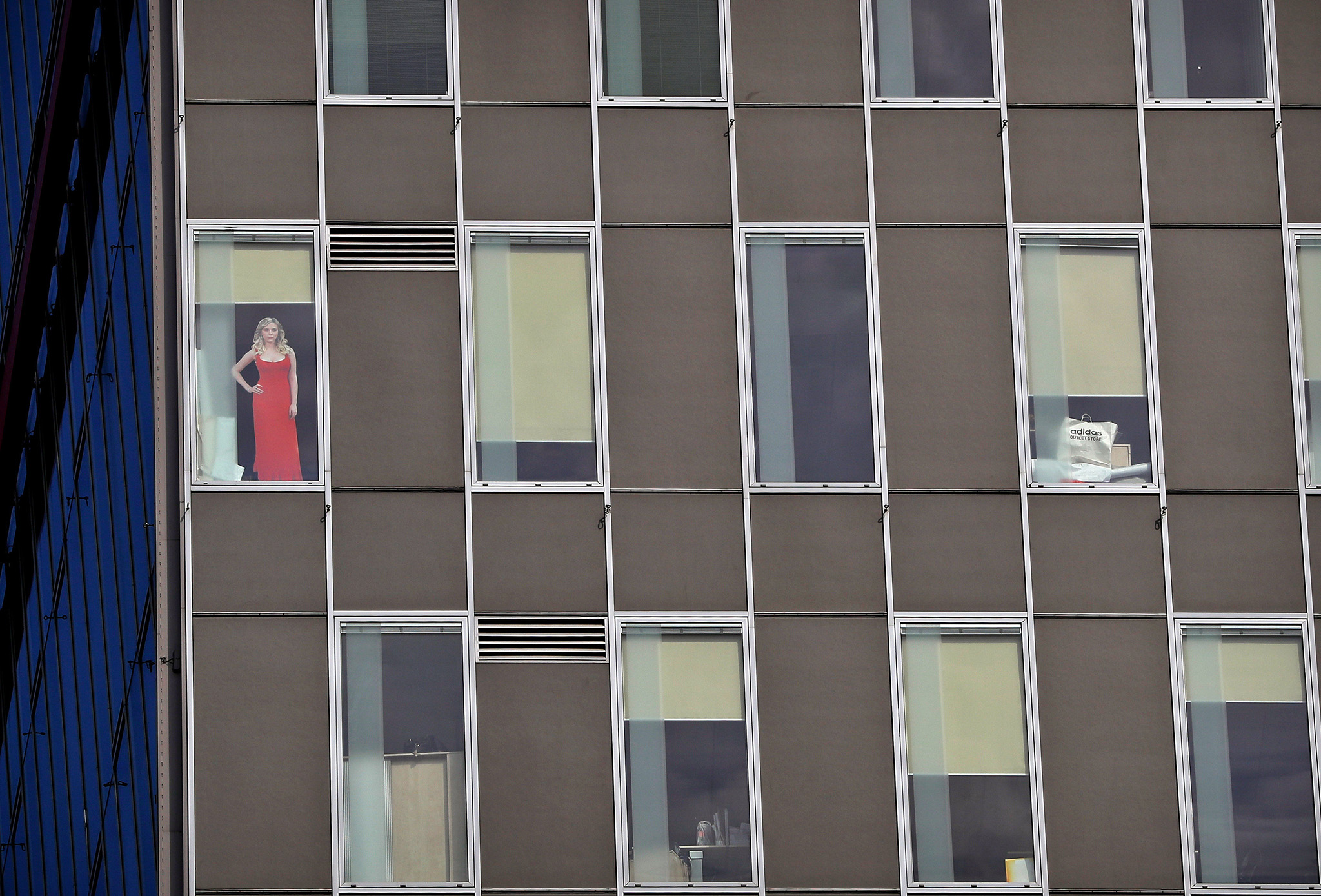 A large cardboard depiction of a woman is placed in one of the windows of an office building in Bucharest, Romania, Thursday, Sept. 15, 2016. (AP Photo/Vadim Ghirda)