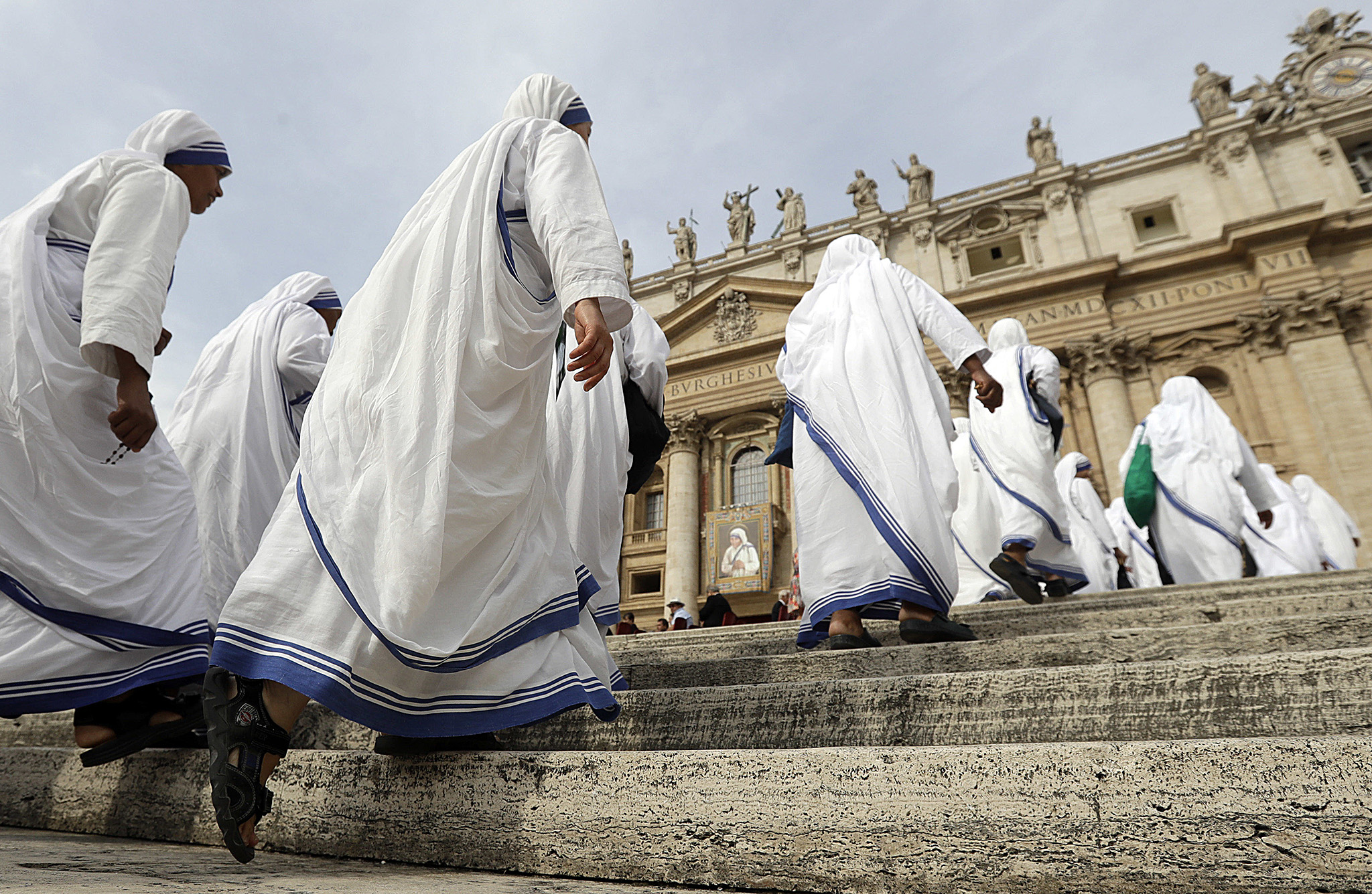 "Sisters of Mother Teresa's Missionaries of Charity walk up the steps to take their seats beneath St. Peter's Basilica for a thanksgiving Mass following Mother Teresa's canonization, in St. Peter's Square, at the Vatican, Monday, Sept. 5, 2016. Elevating the ""saint of the gutters"" to one of the Catholic Church's highest honors, Pope Francis on Sunday praised Mother Teresa for her radical dedication to society's outcasts and her courage in shaming world leaders for the ""crimes of poverty they themselves created."" (AP Photo/Gregorio Borgia)"