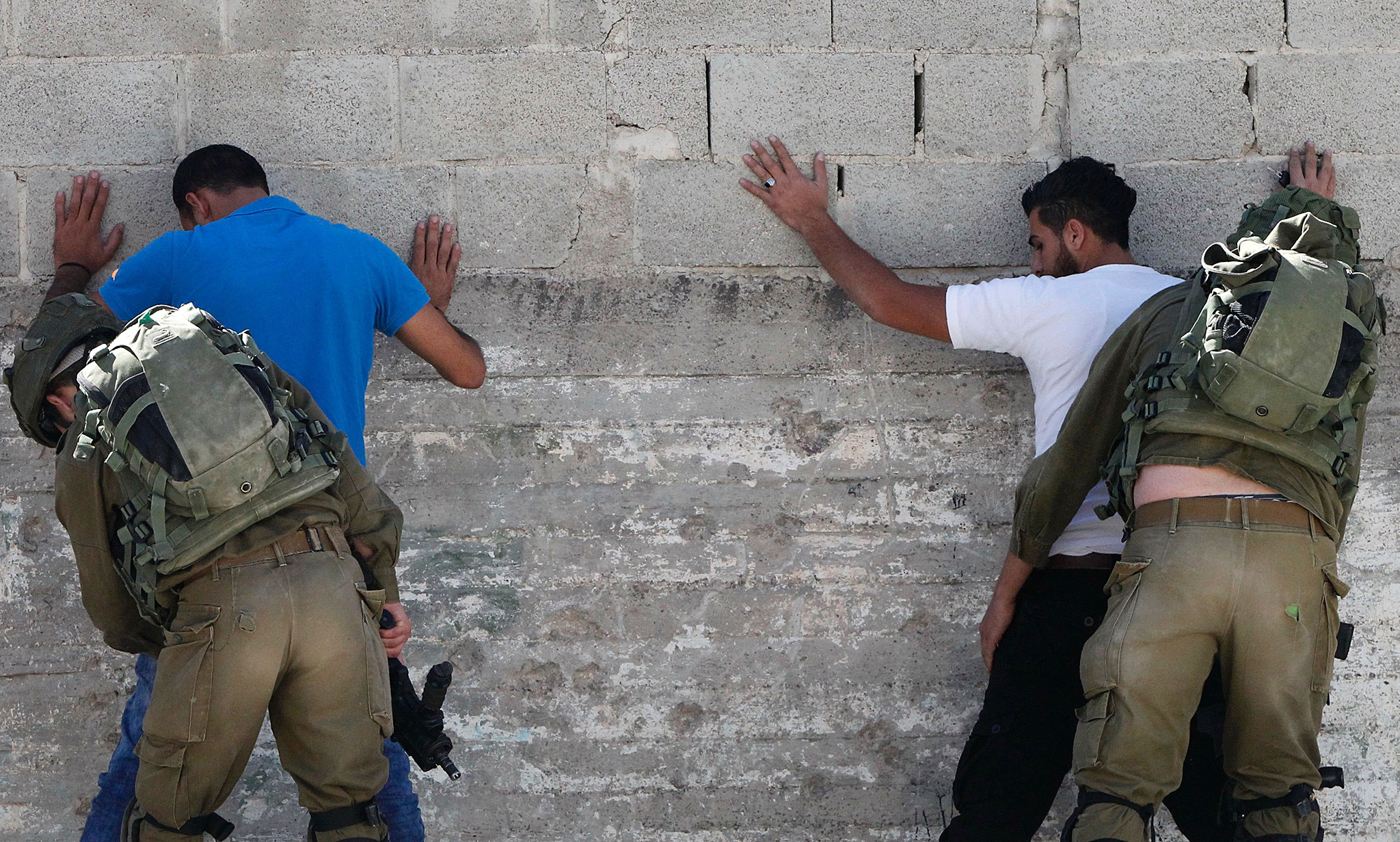 Israeli security forces body search Palestinians in the West Bank town of Hebron on September 20, 2016, after a Palestinian tried to stab Israeli soldiers before being shot to death at a checkpoint at the entrance of the nearby village of Bani Naim.  This incident was the ninth since September 16, 2016, coming after Palestinians wrapped up the Muslim celebration of Eid al-Adha and as Israel tightened security ahead of major Jewish holidays in October.   / AFP PHOTO / HAZEM BADERHAZEM BADER/AFP/Getty Images