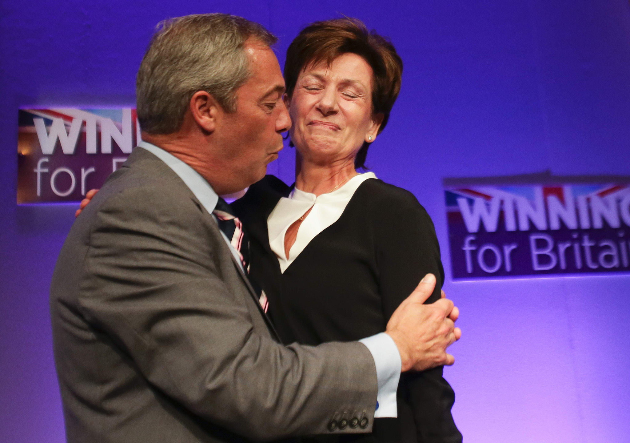 Outgoinng leader Nigel Farage (L) embraces new leader of the anti-EU UK Independence Party (UKIP) Diane James (R) as she is introduced at the UKIP Autumn Conference in Bournemouth, on the southern coast of England