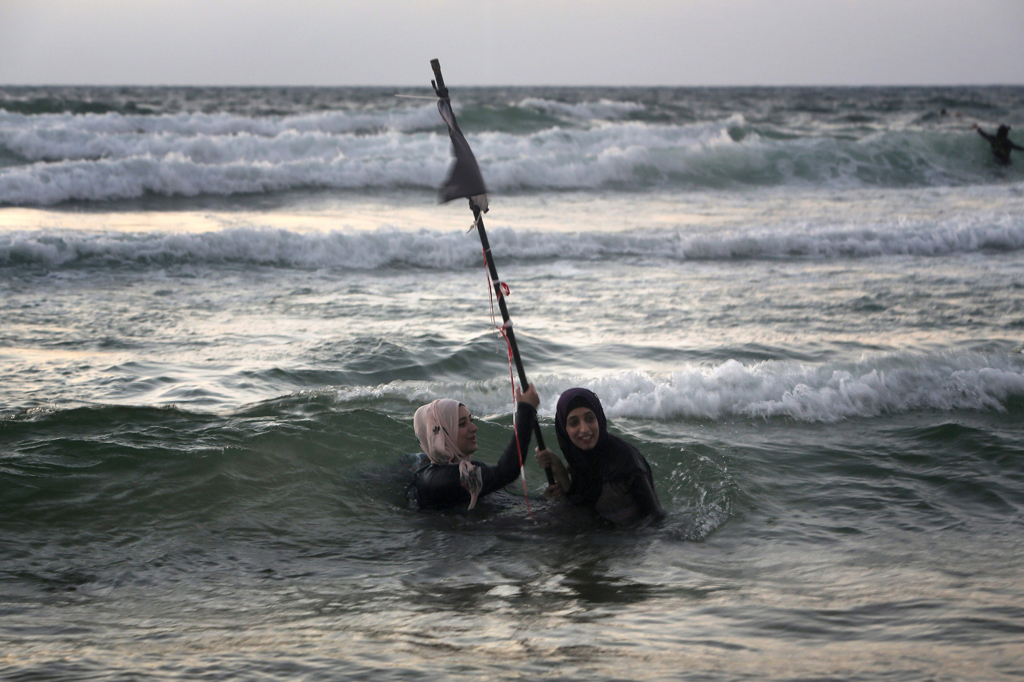 Palestinian women swim in the Mediterranean sea on the beach in Tel Aviv during the Eid al-Adha holiday