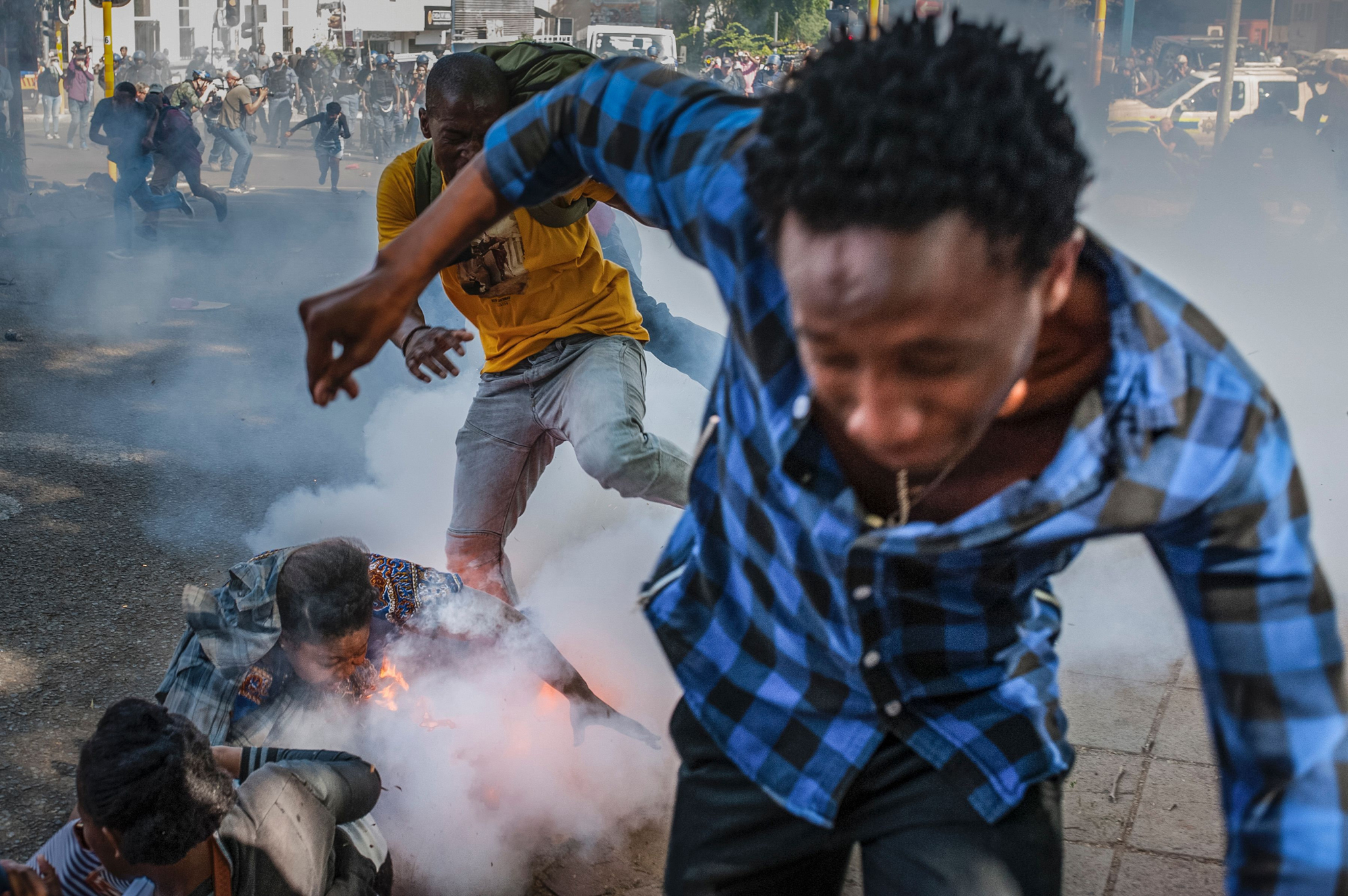 Students from the University of the Witwatersrand are injured by a police grenade during a protest against university fee increases