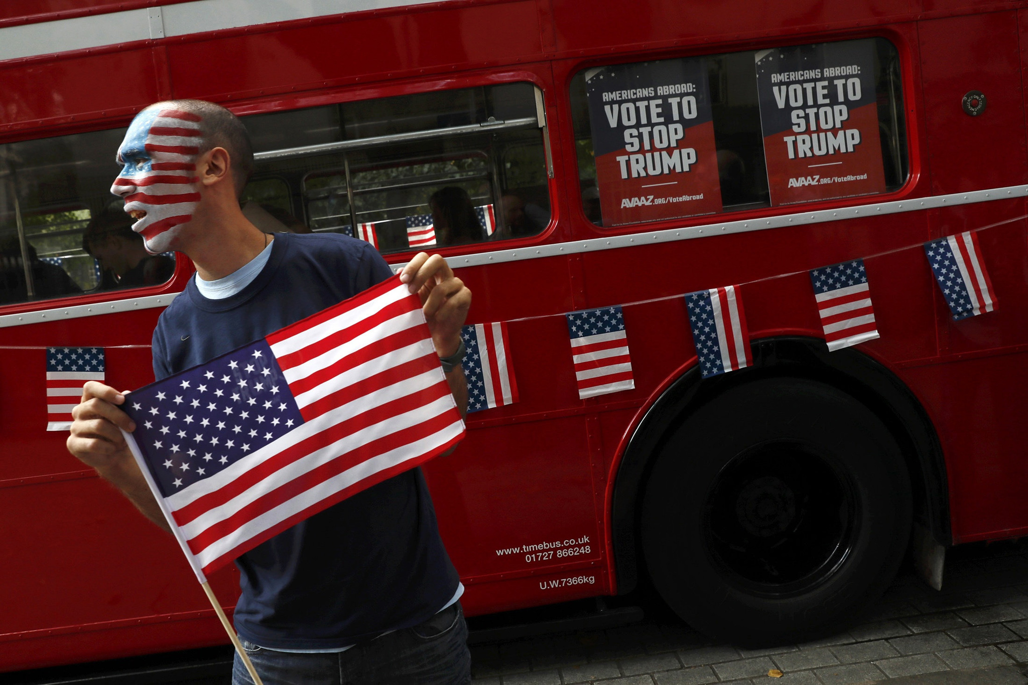 A campaigner holds an American flag in front of a 'Stop Trump' open-top double decker bus before touring London to urge Americans living abroad to register and vote, Britain