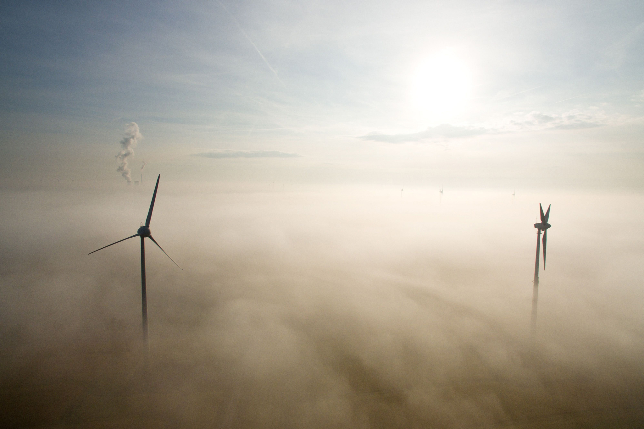 Windmills are seen through the morning mist rising from a field in Sehnde near Hanover, northern Germany
