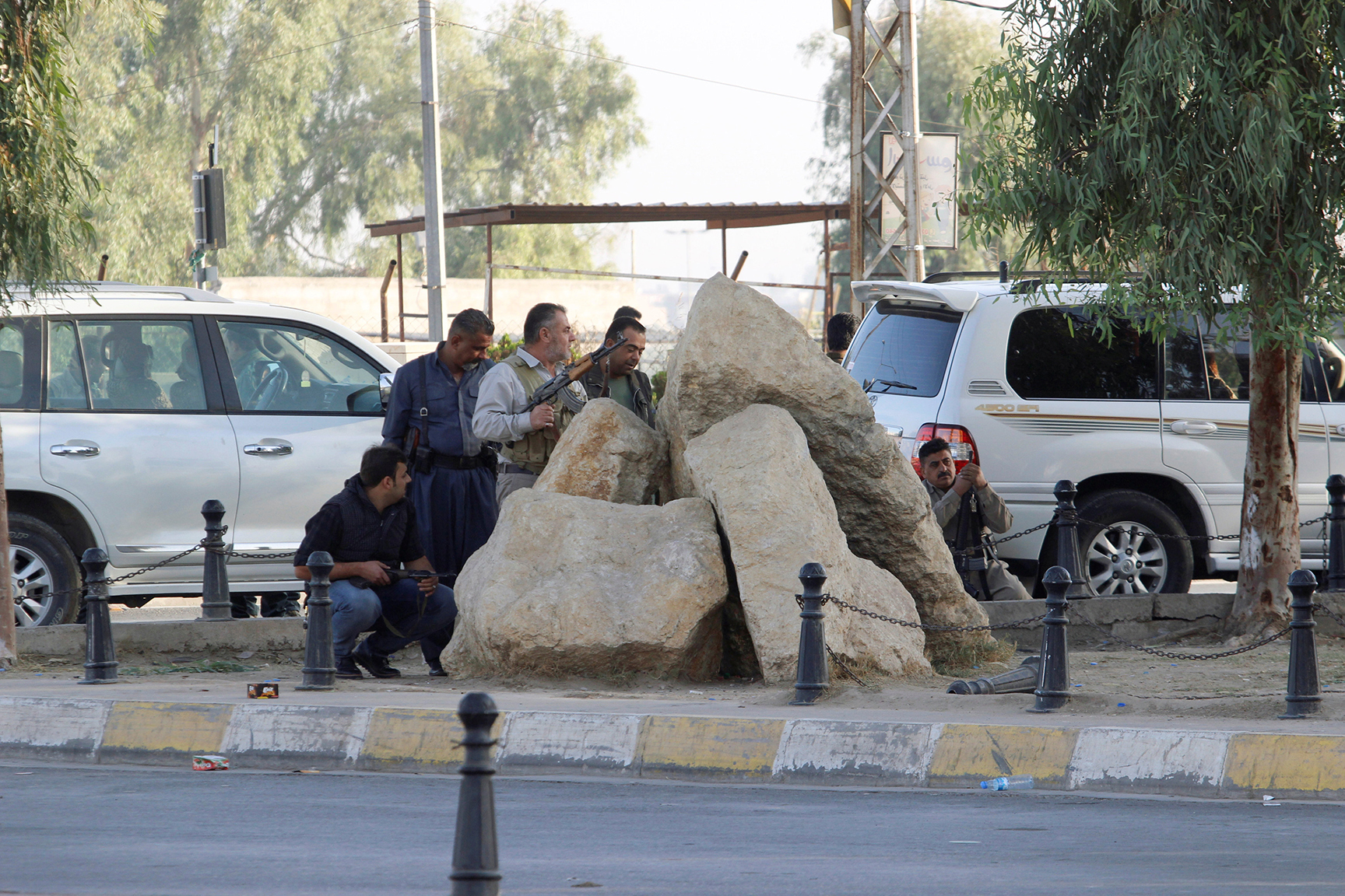 Peshmerga forces stand behind rocks at a site of an attack by Islamic State militants in Kirkuk