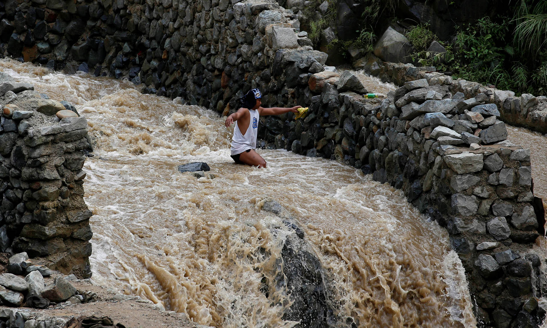 A local miner wades through water as he walks down from a mountain in Benguet a day after Typhoon Haima struck northern Philippines