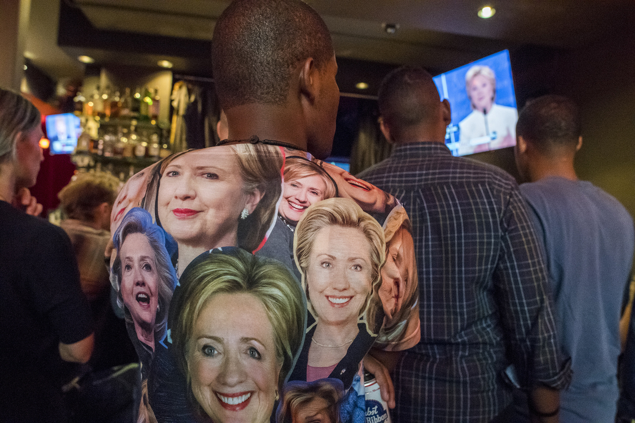 A man wears a shirt with photographs of Hillary Clinton, 2016 Democratic presidential nominee, while watching the third U.S. presidential debate at a viewing party in San Francisco, California, U.S., on Wednesday, Oct. 19, 2016. Donald Trump is trying another wild-card play in the third and final presidential debate with Hillary Clinton in perhaps his last chance to reverse his campaign's spiral and halt his Democratic rival's rising electoral strength. Photographer: David Paul Morris/Bloomberg