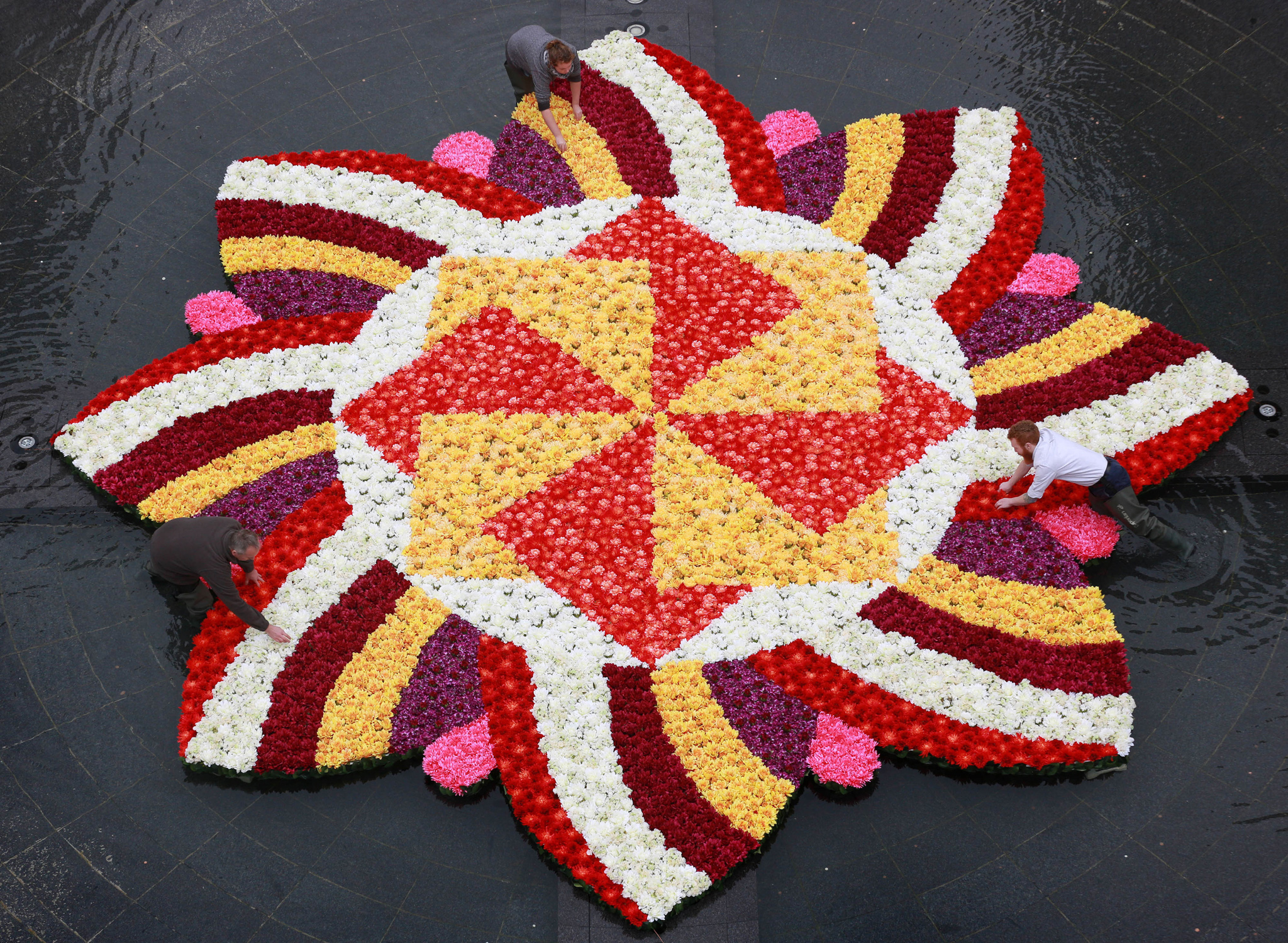 Floral artists (left-right) Richard Bragg, Harriet Sargent and James Buswell put the finishing touches to a 9x9m rangoli-style flower installation in the fountain at Cabot Square, Canary Wharf, London, made with over 6,000 flowers to celebrate Diwali, the Festival of Light.