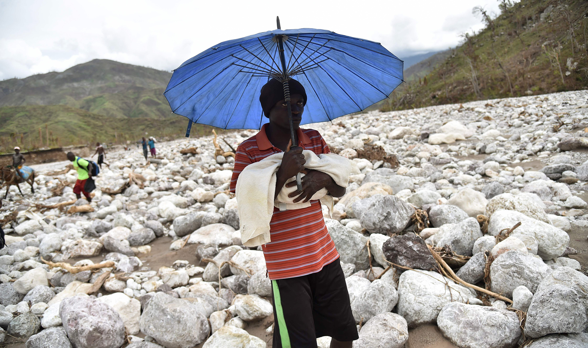 TOPSHOT - A man carries his baby on a trail in the middle of the river that passes near the village of Randelle, in the commune of Chardonniere, in the south west of Haiti, on October 19, 2016. The road leading to Randelle and other villages on the mountains was cut off after the passage of Hurricane Matthew. / AFP PHOTO / HECTOR RETAMALHECTOR RETAMAL/AFP/Getty Images