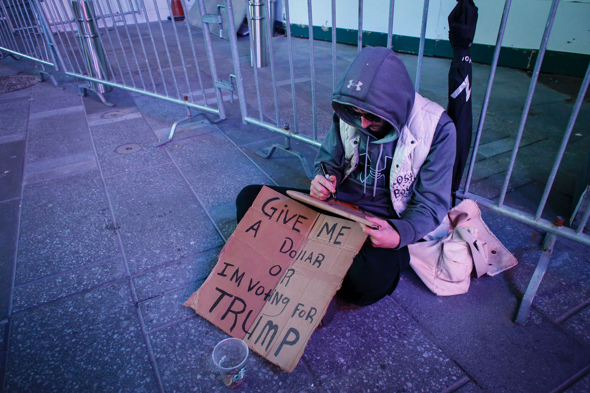 A man begs for money as he displays a placard during the second presidential debate Times Square in New York on October 9, 2016. / AFP PHOTO / KENA BETANCURKENA BETANCUR/AFP/Getty Images