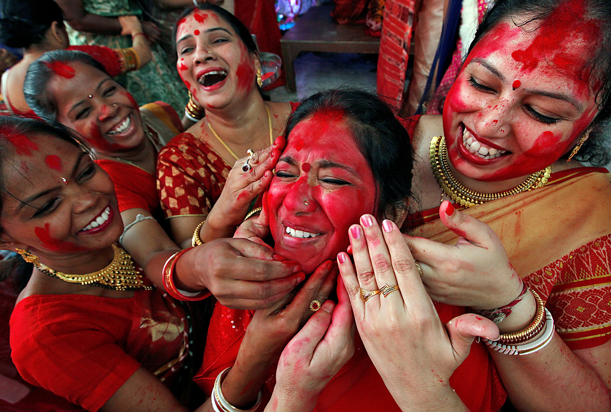 "Hindu women apply ""sindhur"", or vermillion powder, on the face of a woman after worshipping the idol of the Hindu goddess Durga on the last day of the Durga Puja festival in Chandigarh, India October 11, 2016."