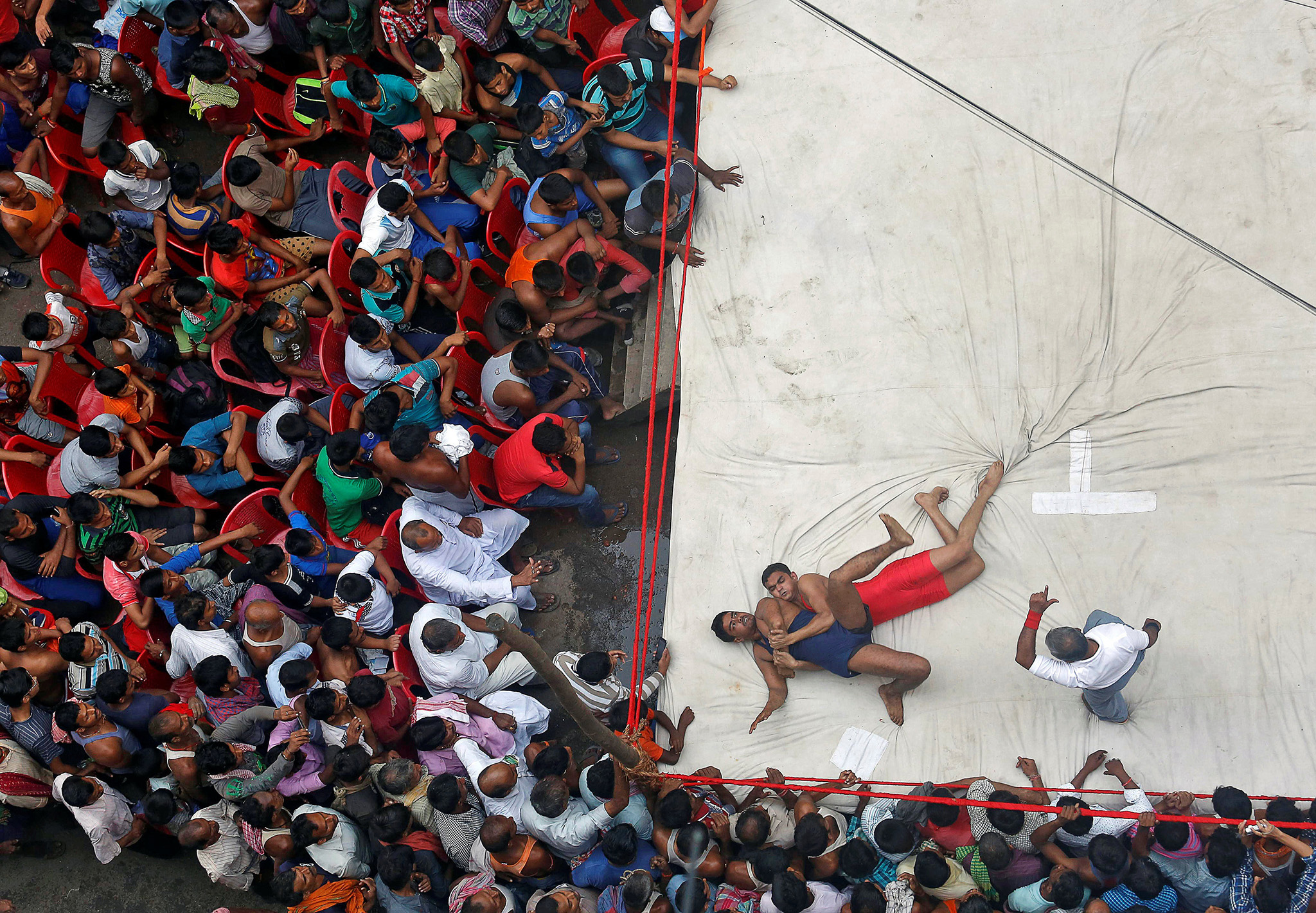 Wrestlers fight during an amateur wrestling match inside a makeshift ring installed on a road organised by local residents as part of the celebrations for the annual Hindu festival of Diwali in Kolkata, India, October 27, 2016. REUTERS/Rupak De Chowdhuri