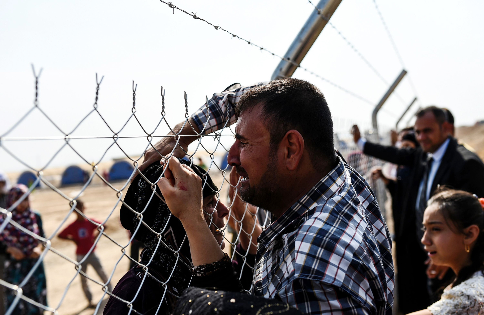 Newly displaced Iraq's who fled from the city of Mosul, Iraq's last major Islamic State (IS) group stronghold, cry as they meet their relatives who came two years ago to the refugee camp in the Khazer area, near near the Kurdish checkpoint of Aksi Kalak, some 40 kilometres east of Arbil following their arrival on October 26, 2016.  The United Nations Office for the Coordination of Humanitarian Affairs (OCHA) Stephane Dujarric told reporters that almost 9,000 people are internally displaced as a result of the Mosul military operation in Iraq. Lise Grande, the U.N. humanitarian coordinator for Iraq, said the military operations to retake Mosul could spark the largest humanitarian crisis in 2016 as the security situation in the area restrains aid agencies' ability to deliver help. / AFP PHOTO / BULENT KILICBULENT KILIC/AFP/Getty Images