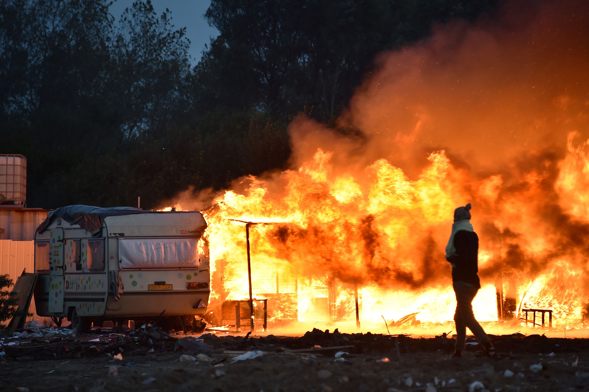 "A woman walks past a burning structure at the ""Jungle"" migrant camp in Calais, northern France, early on October 28, 2016, after a massive operation to clear the settlement where 6,000-8,000 people have been living. Migrants left behind after the demolition of France's notorious ""Jungle"" faced a day of reckoning on October 28 after spending the night, with official blessing, in a disused part of the camp. / AFP PHOTO / PHILIPPE HUGUENPHILIPPE HUGUEN/AFP/Getty Images"