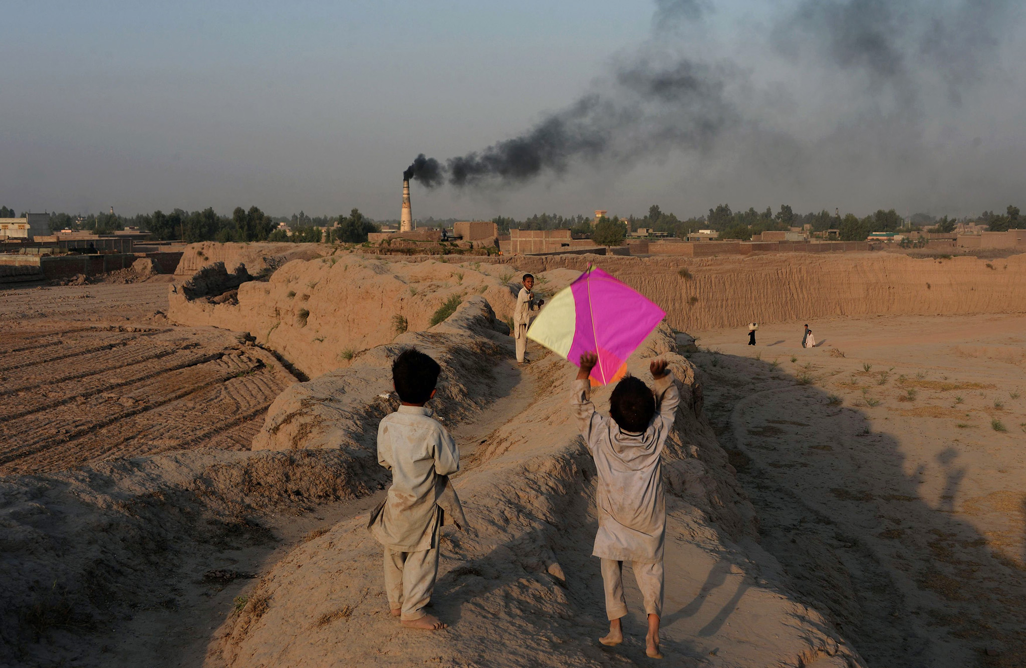 This photograph taken on October 18, 2016 shows Afghan youths playing with a kite on the outskirts of Jalalabad.
