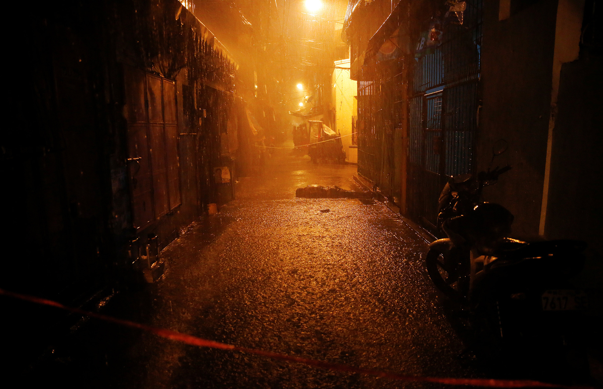 Heavy rain pours as the body of a man killed by unidentified gunmen riding motorcycles is left in a narrow alley in Manila, Philippines early October 11, 2016. REUTERS/Damir Sagolj TEMPLATE OUT