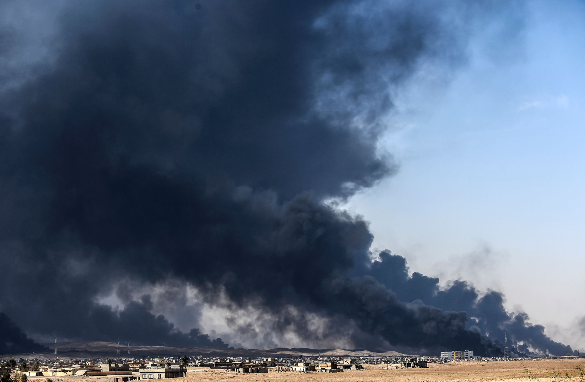 "Smoke rises from burning oil wells on October 18, 2016 near the town of Qayyarah, south of Mosul, during the operation to recapture the city from the Islamic State group. Tens of thousands of Iraqi forces were making gains on the Islamic State group in Mosul in an offensive US President Barack Obama warned would be a ""difficult fight"".  / AFP PHOTO / BULENT KILICBULENT KILIC/AFP/Getty Images"