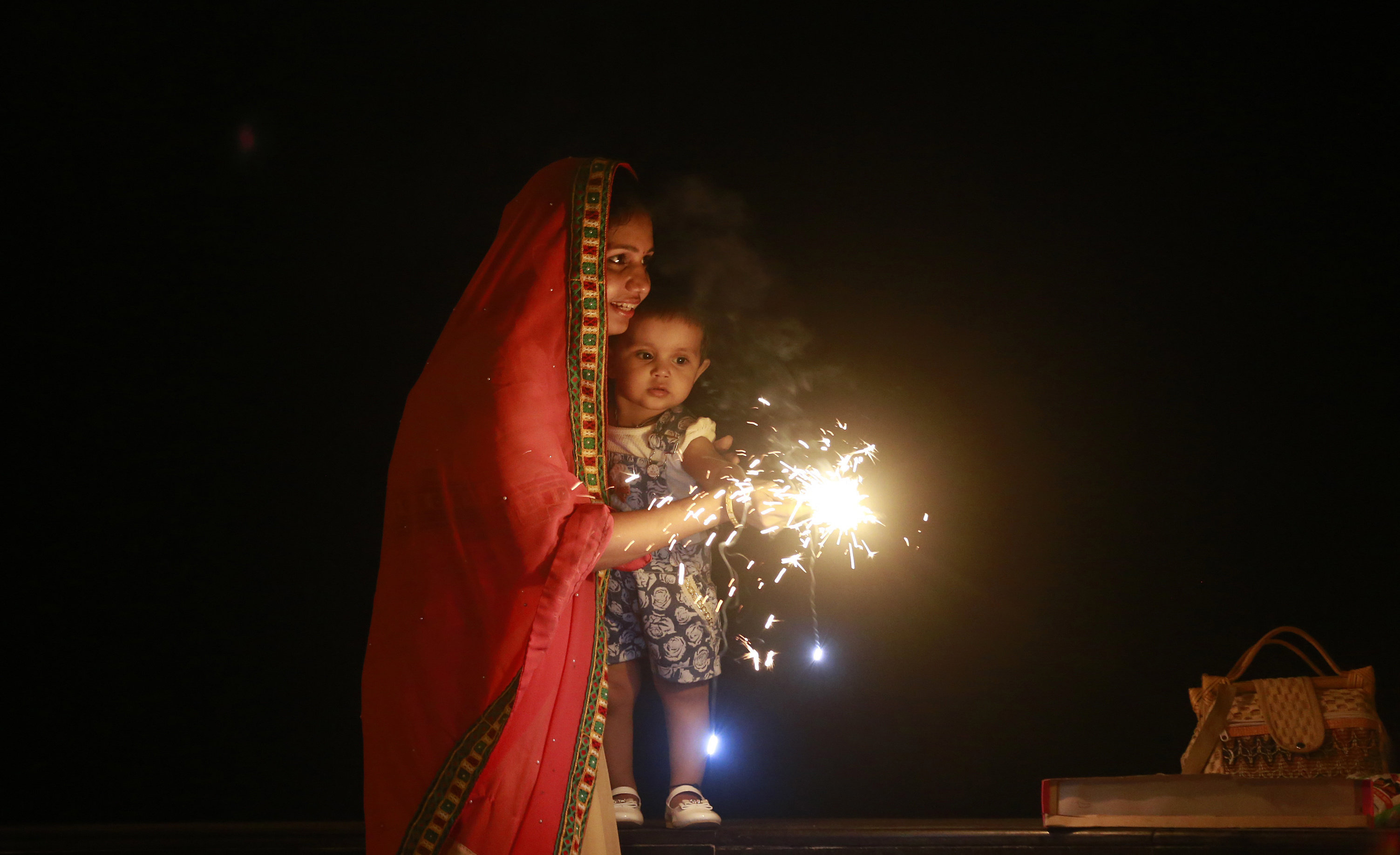 A Hindu woman lights a firecrackers with her daughter to celebrate Diwali, the Hindu festival of lights, in Mumbai, India