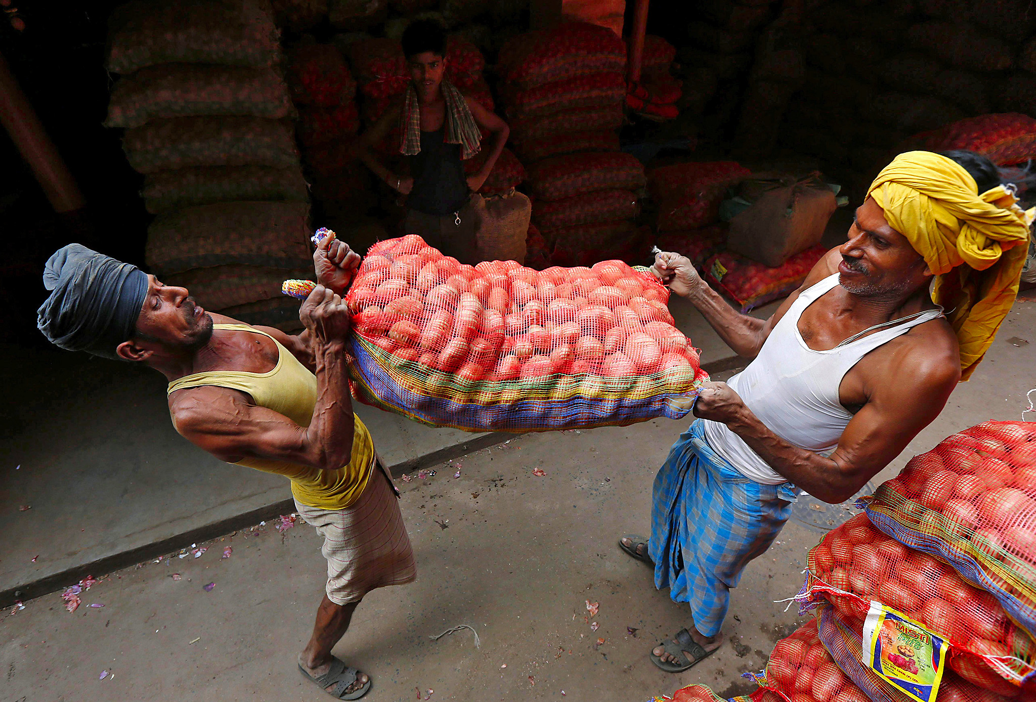 Labourers lift a sack of potatoes to load onto a supply truck at a wholesale market in Kolkata, India, October 14, 2016. REUTERS/Rupak De Chowdhuri