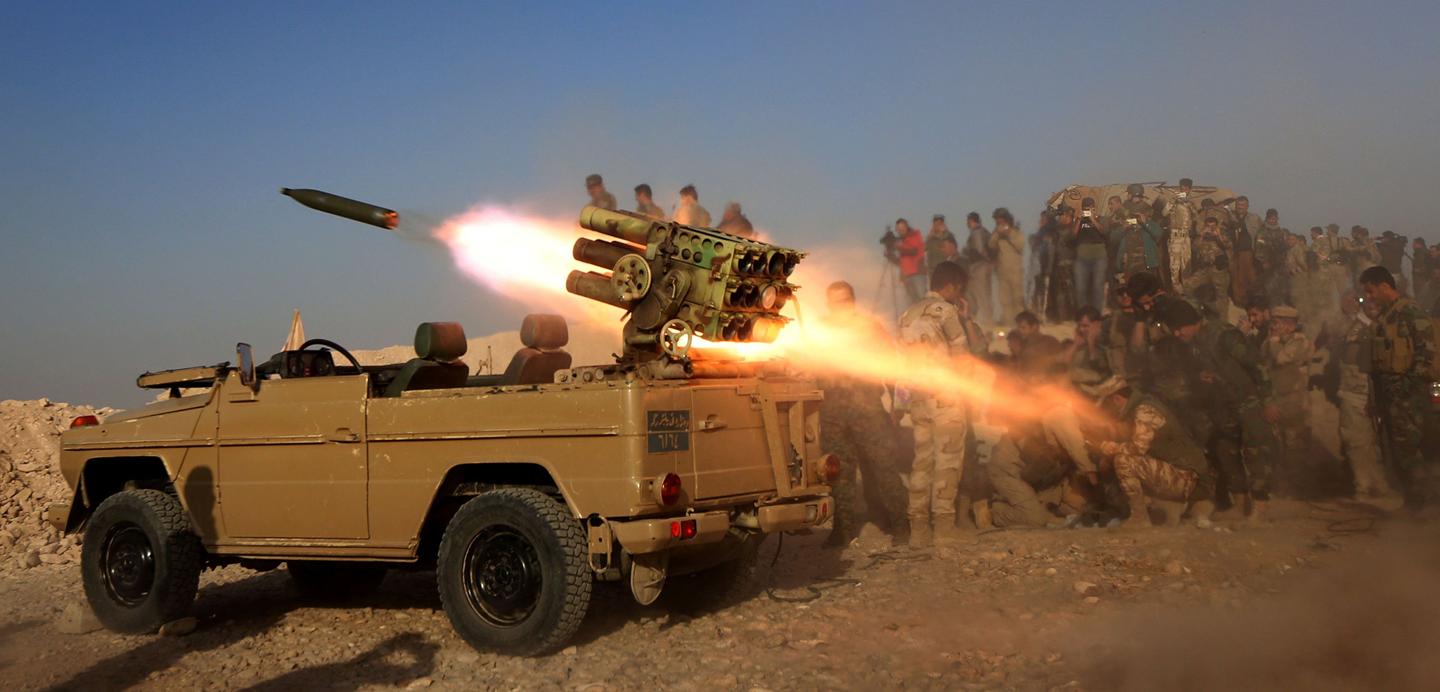 Iraqi Kurdish Peshmerga fighters fire a multiple rocket launcher from a position in Sheikh Ali village near the town of Bashiqa, some 25 kilometres north east of Mosul during an operation against Islamic State group jihadists to retake the main hub city.