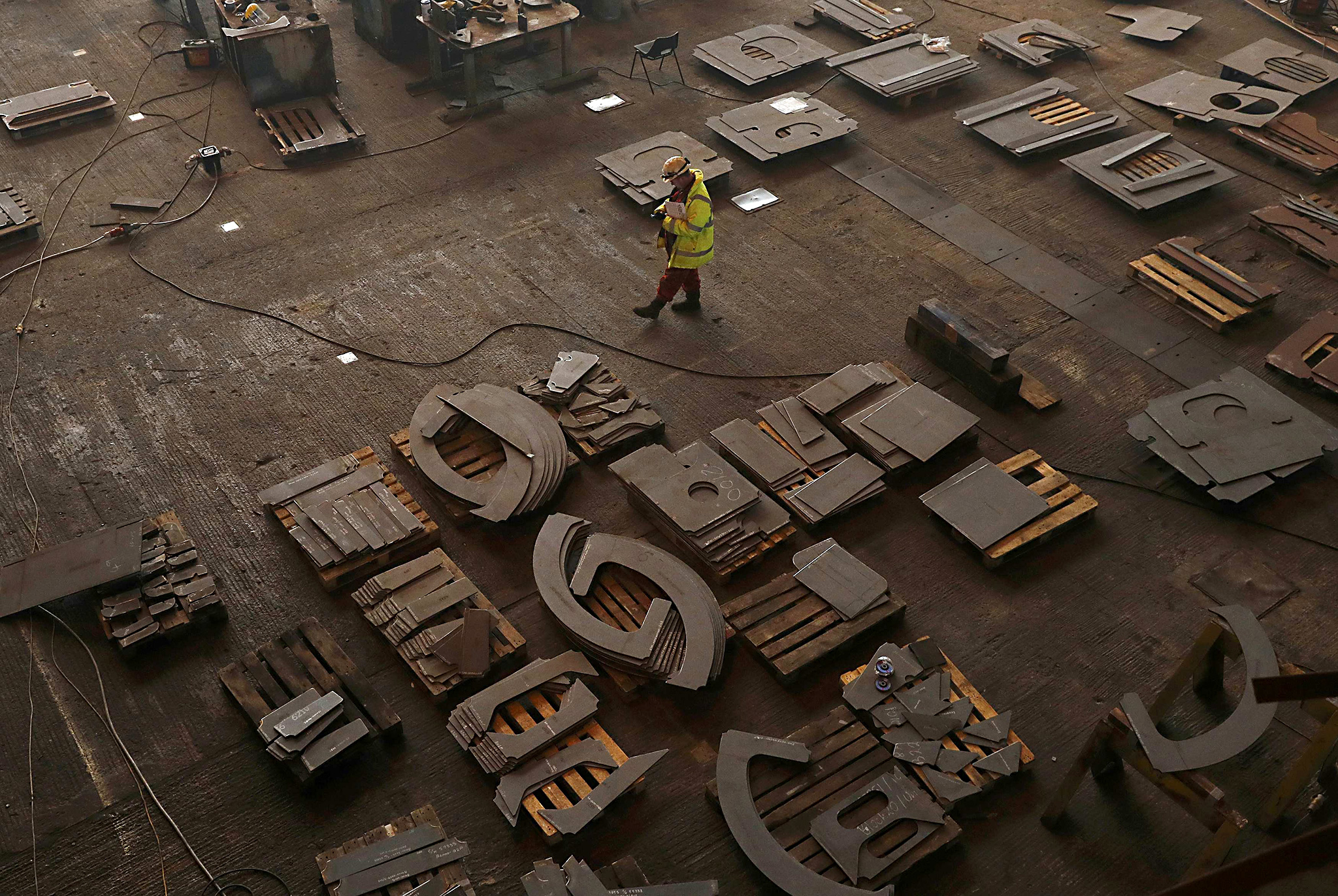A shipyard worker walks across the construction hall after attending the keel laying ceremony of the new polar research vessel the Sir David Attenborough, at the Cammell Laird ship yard in Birkenhead, northern England October 17 , 2016. REUTERS/Phil Noble