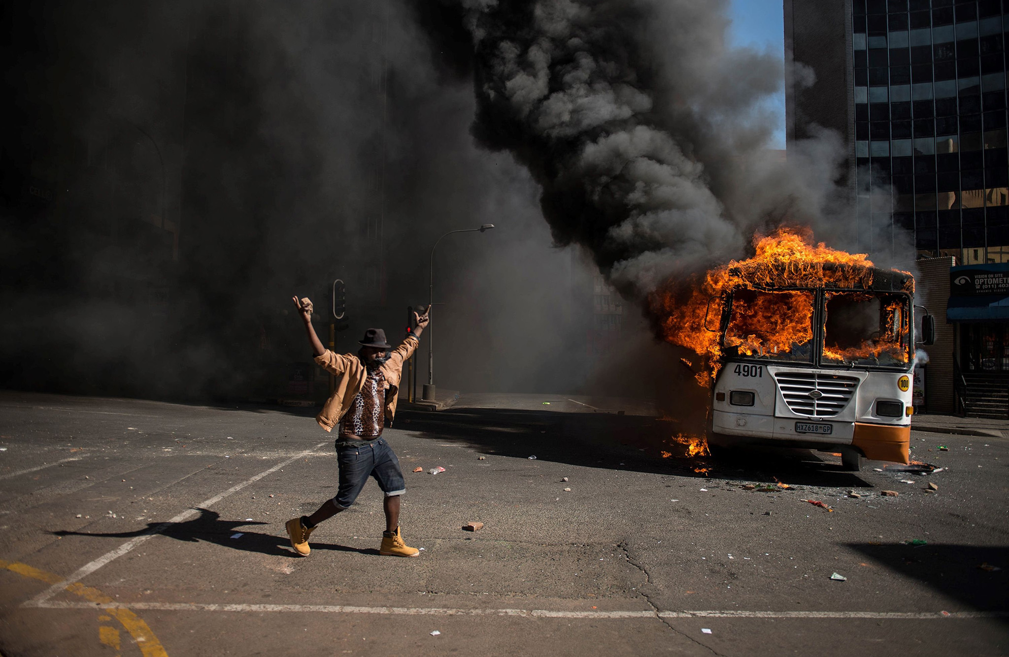 A student gestures near a burning bus during clashes with riot police following a protest over University tuition fees on October 10, 2016 in Johannesburg.  South African student protesters and police clashed in renewed violence in Johannesburg as attempts to re-open Wits University descended into running battles on campus. Protesters throwing rocks were dispersed by riot police using tear gas, rubber bullets and stun grenades as pressure ratchets up on campuses across the country over tuition fees.  / AFP PHOTO / MUJAHID SAFODIENMUJAHID SAFODIEN/AFP/Getty Images