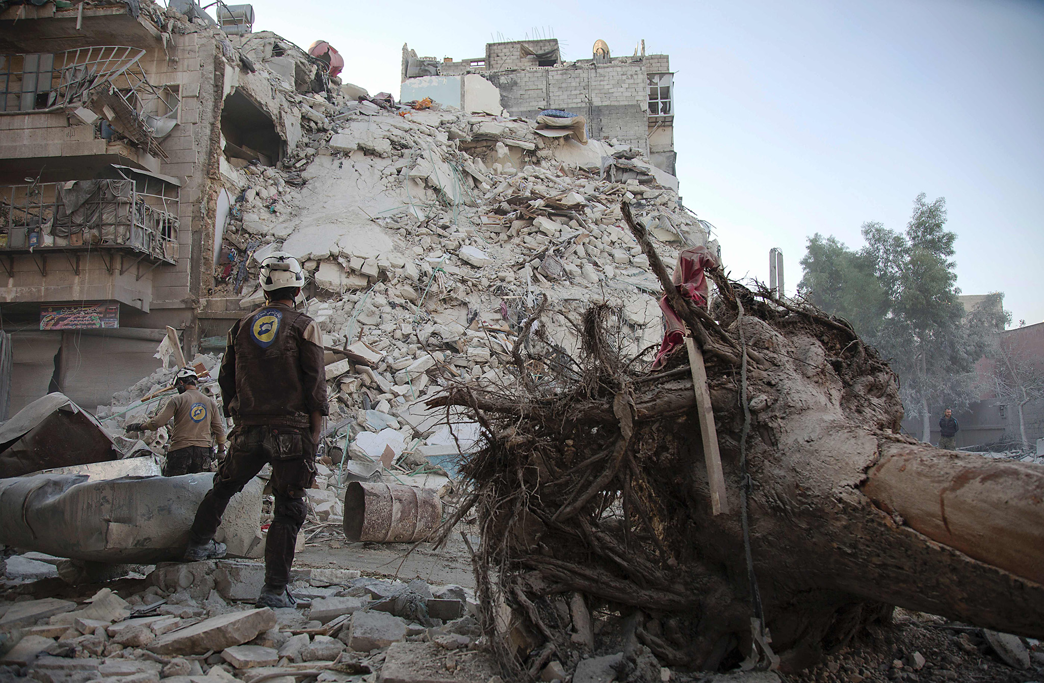 A member of the Syrian Civil Defence, known as the White Helmets, stands amid the rubble of a destroyed building during a rescue operation following reported air strikes in the rebel-held Qatarji neighbourhood of the northern city of Aleppo, on October 17, 2016.  Dozens of civilians were killed as air strikes hammered rebel-held parts of Aleppo early morning, despite Western warnings of potential sanctions against Syria and Russia over attacks on the city. Both Russian and Syrian warplanes are carrying out air strikes over Aleppo in support of a major offensive by regime forces to capture rebel-held parts of the northern city.  / AFP PHOTO / KARAM AL-MASRIKARAM AL-MASRI/AFP/Getty Images