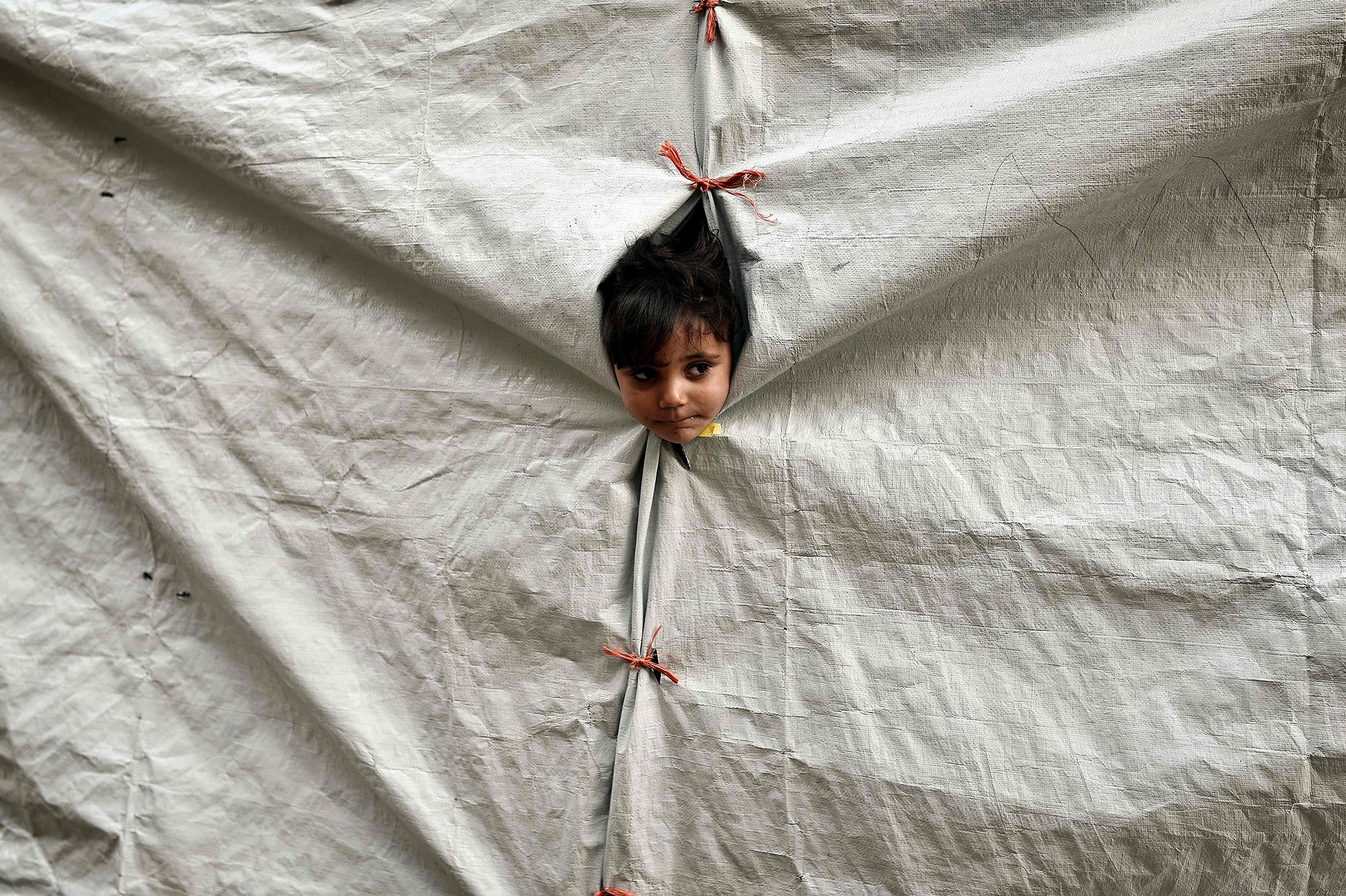 A child peers out of her tent at the Souda municipality-run refugee camp on the Greek island of Chios on October  13, 2016.  Greece is accommodating over 60,000 refugees and migrants stuck in the country after a succession of Balkan and EU states shut their borders earlier this year. / AFP PHOTO / LOUISA GOULIAMAKILOUISA GOULIAMAKI/AFP/Getty Images