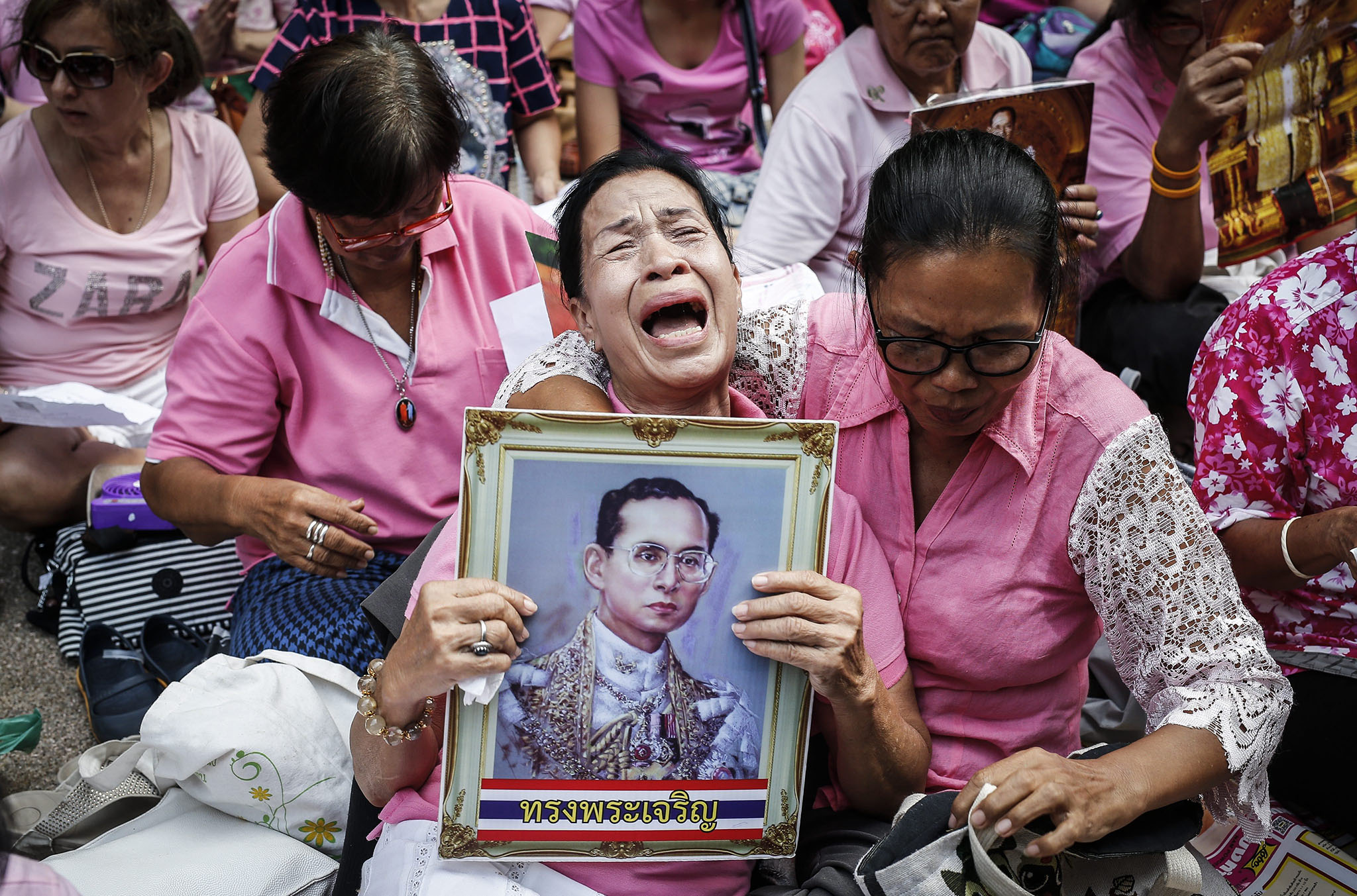 A Thai well-wisher weeps as she is comforted by others during a prayer for Thai King Bhumibol Adulyadej's recovery at the Siriraj Hospital in Bangkok,