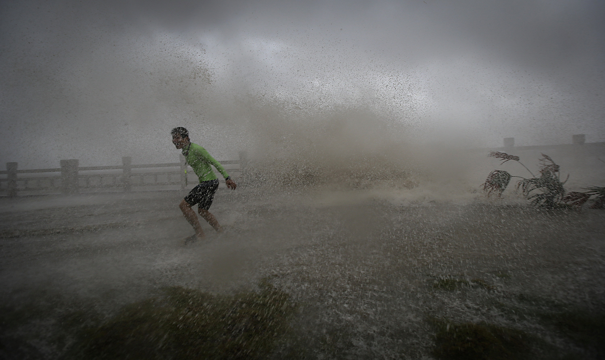 A man playing with waves runs way from a wave at a beach as Typhoon Sarika lands in Wanning, Hainan province, China, October 18, 2016. REUTERS/Stringer ATTENTION EDITORS - THIS IMAGE WAS PROVIDED BY A THIRD PARTY. EDITORIAL USE ONLY. CHINA OUT. NO COMMERCIAL OR EDITORIAL SALES IN CHINA.