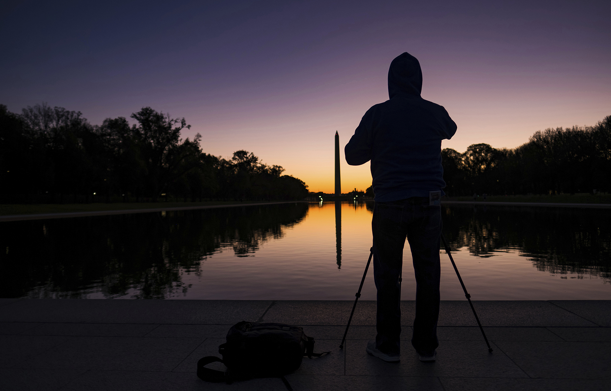 A photographer sets up in front of the Reflecting Pool on the National Mall to capture daybreak behind the Washington Monument, Tuesday, Oct. 25, 2016, in Washington. (AP Photo/J. David Ake)