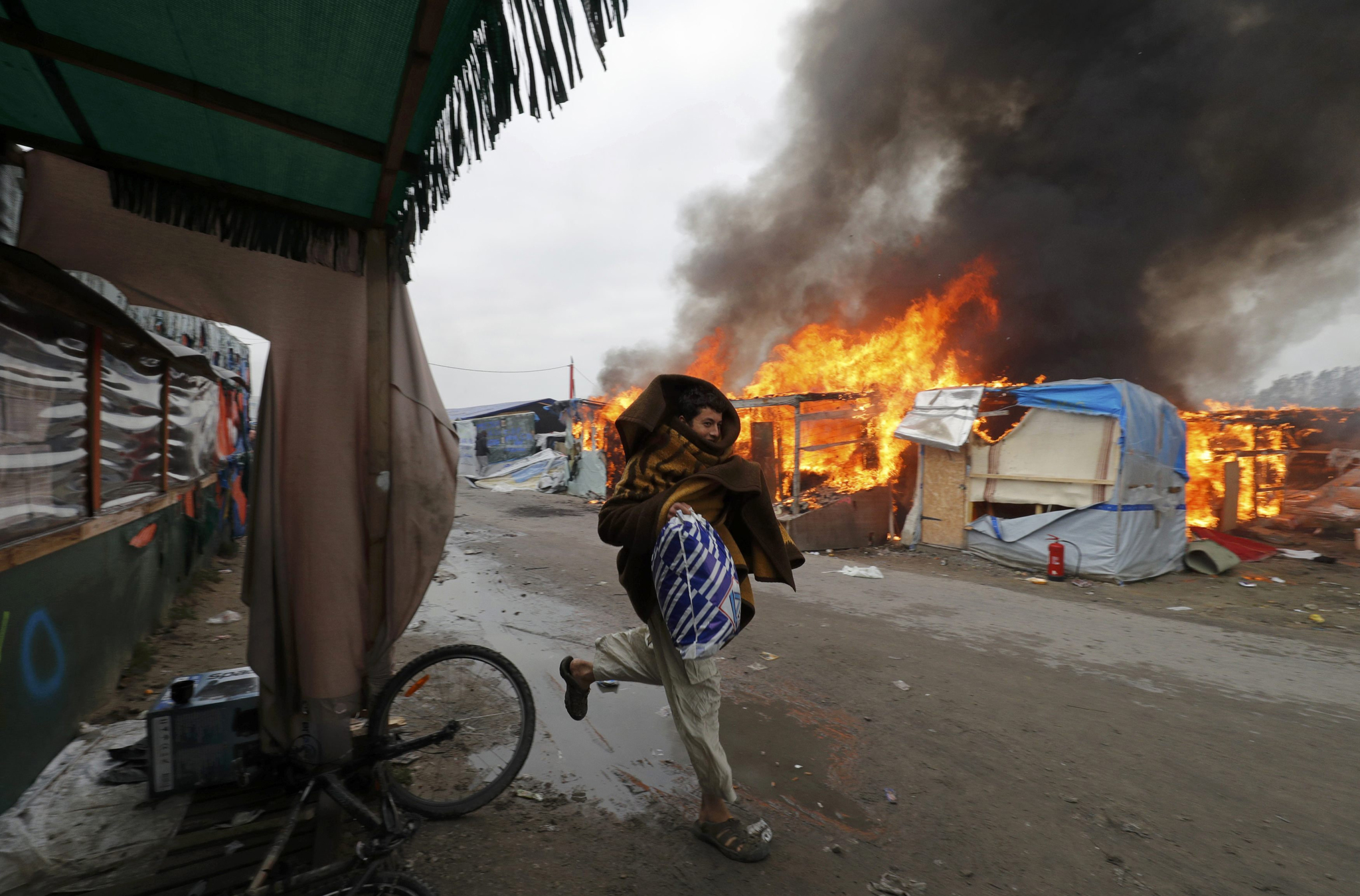"A migrant runs past a burning makeshift shelters in the ""Jungle"" on the third day of their evacuation and transfer to reception centers in France, as part of the dismantlement of the camp in Calais, France"