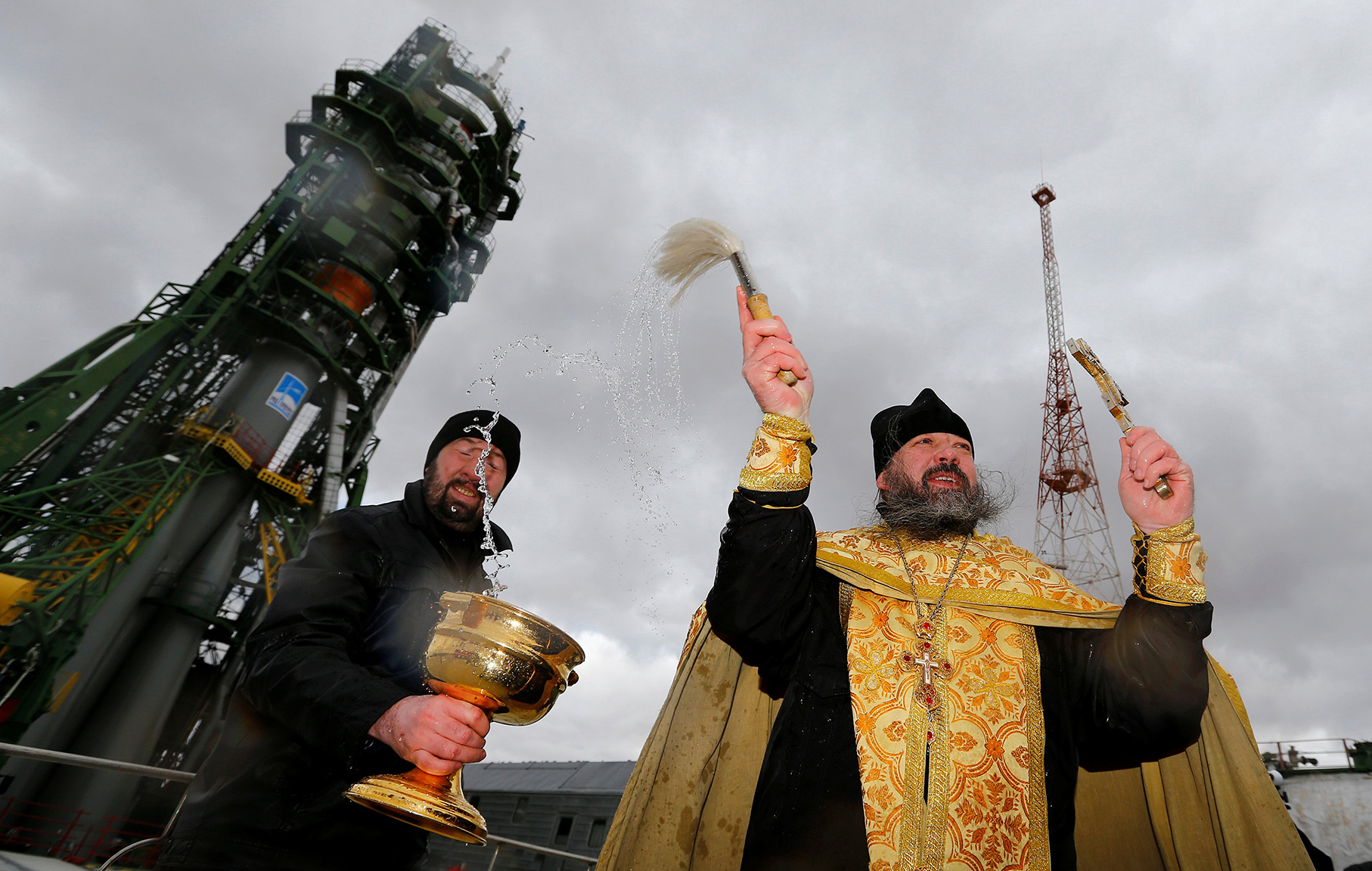 An Orthodox priest conducts a blessing in front of the Soyuz MS-02 spacecraft set on the launch pad at Baikonur cosmodrome