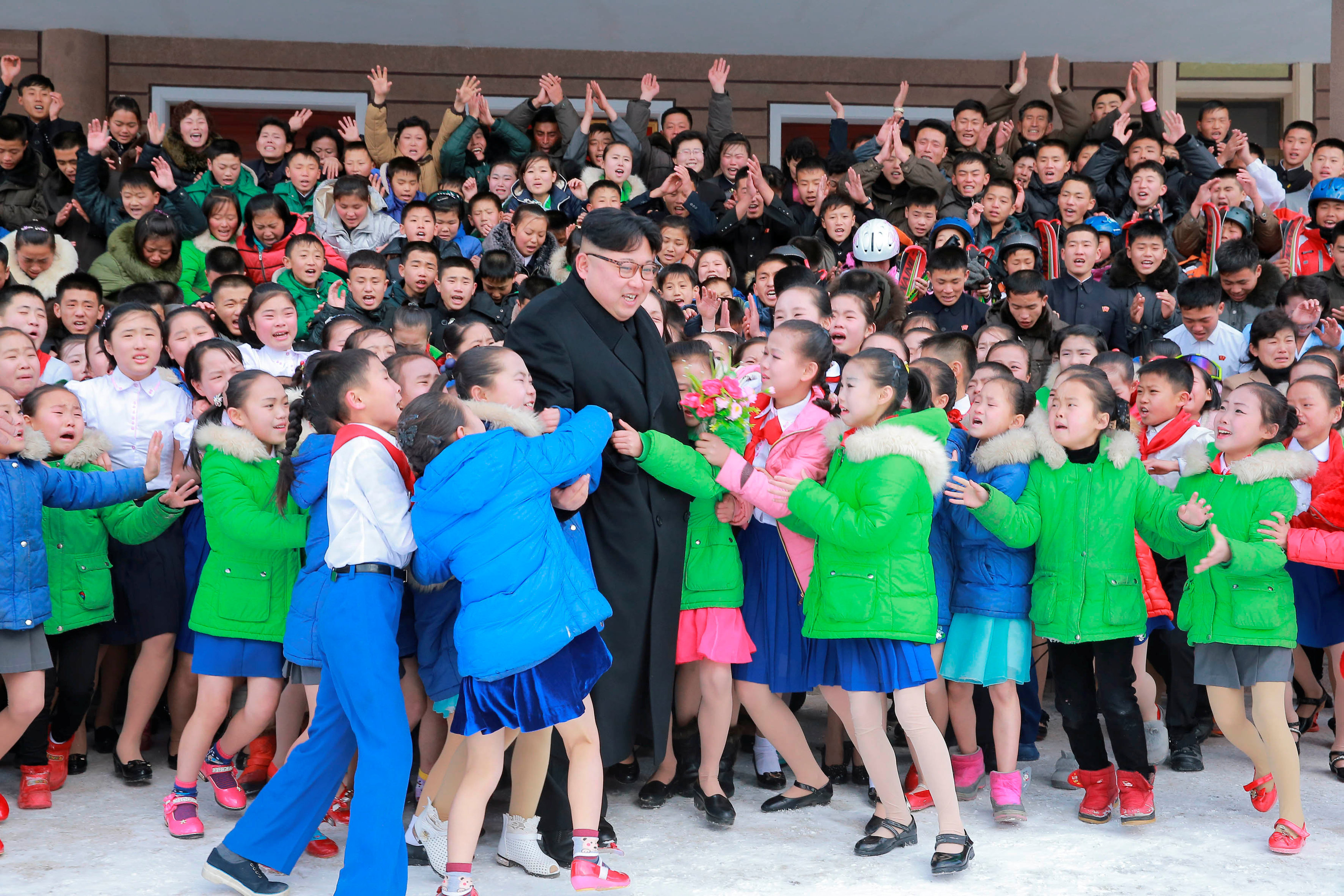 North Korean leader Kim Jong Un is hugged by children during his visit to Samjiyon County