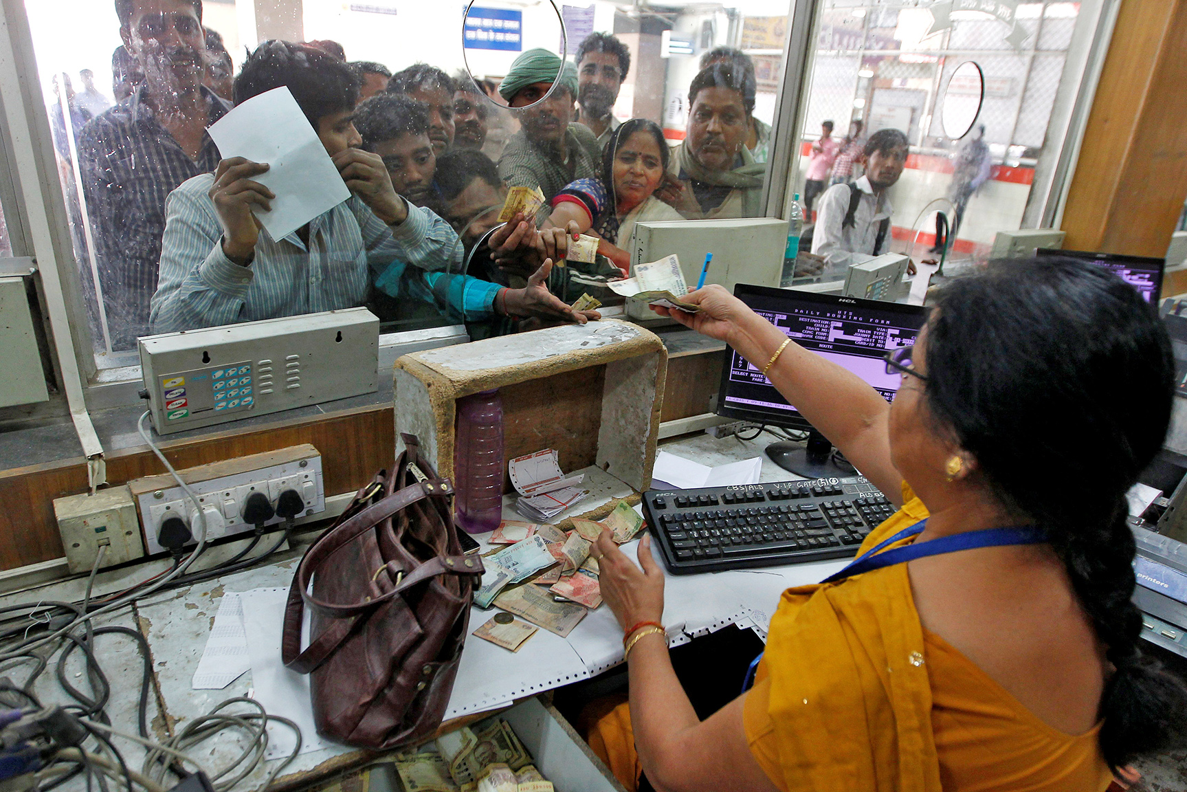 A railway employee returns change to a passenger at a railway booking counter in Allahabad