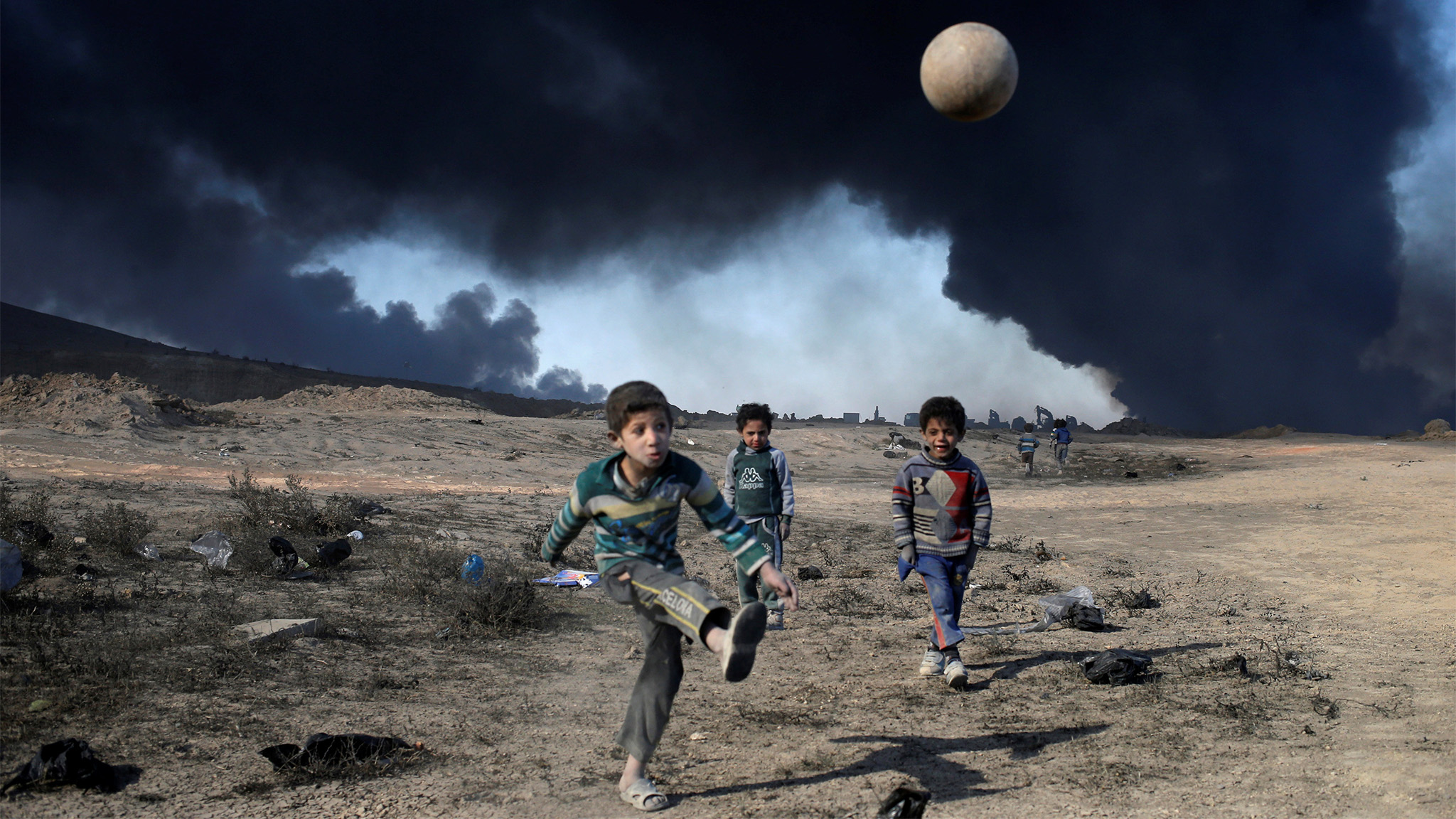 Boys play with a ball in front of oilfields burned by Islamic State fighters in Qayyara