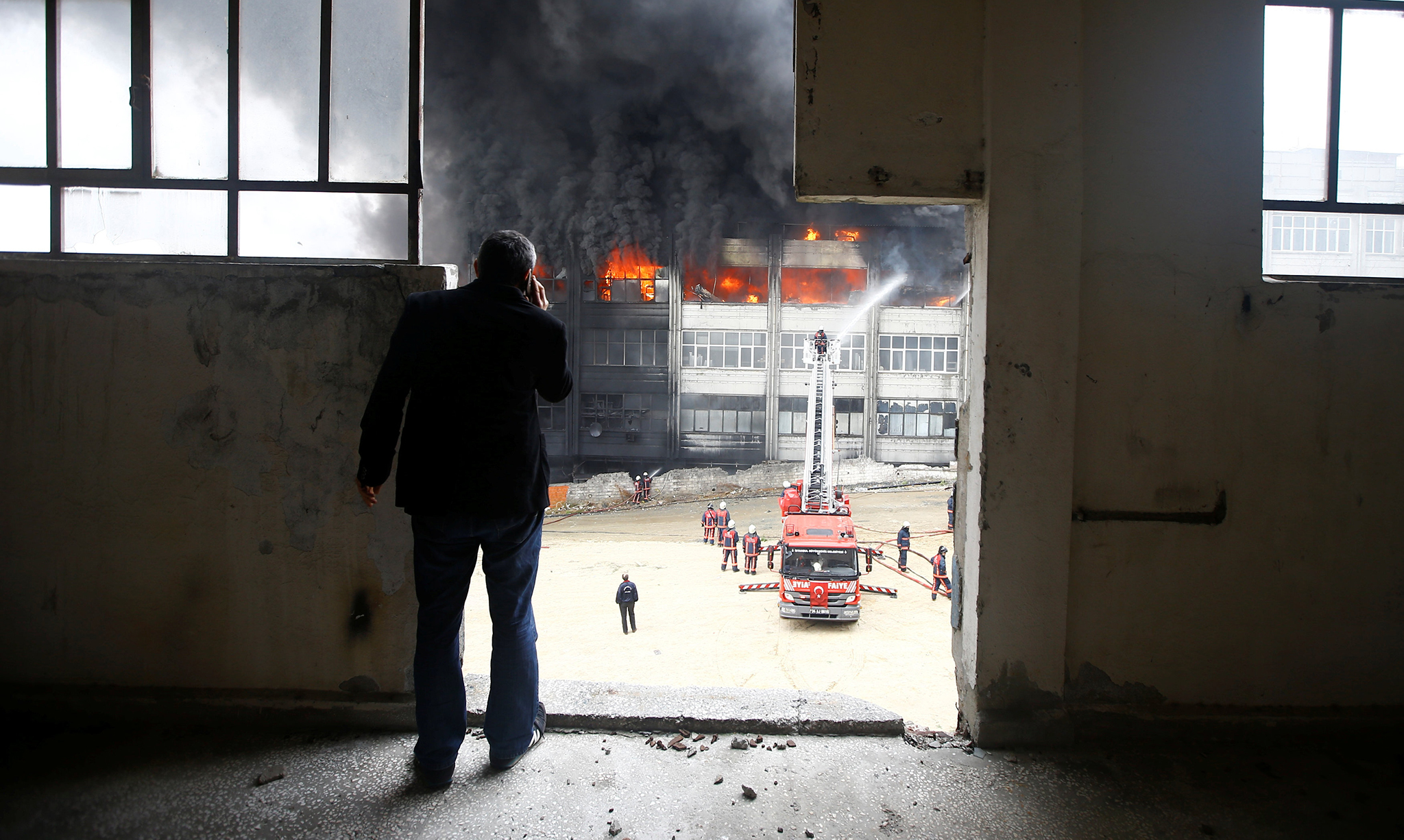 A man watches as firemen try to extinguish a fire at a plastic factory in Istanbul, Turkey, November 22, 2016. The cause of the fire is currently unknown, according to local media. REUTERS/Osman Orsal