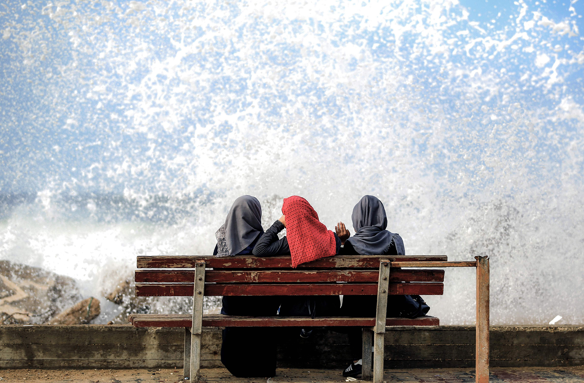 Three Palestinian women sit on a beachfront as a wave comes rushing by in Gaza City on November 17, 2016. / AFP PHOTO / MOHAMMED ABEDMOHAMMED ABED/AFP/Getty Images