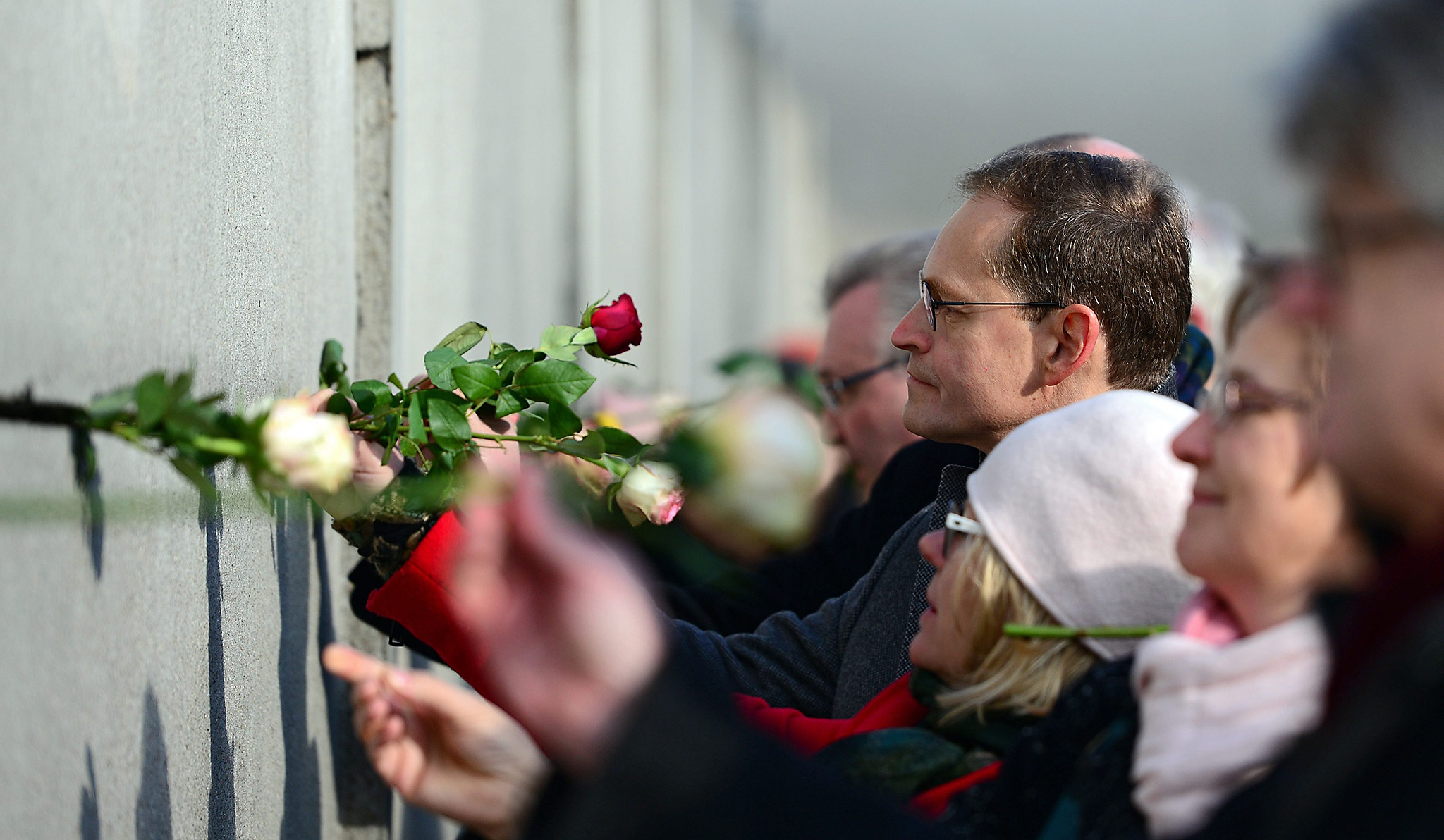 Berlin Mayor Michael Mueller places a rose in a crack during the central event to commemorate the 1989 Peaceful Revolution in the GDR at the Berlin Wall memorial site in Berlin, Germany, 09 November 2016. 09 November marks a significant date in German history when both the Fall of the Wall as well as the Kristallnacht (Cyrstal Night, or Night of Broken Glass) are commemorated.  EPA/MAURIZIO GAMBARINI