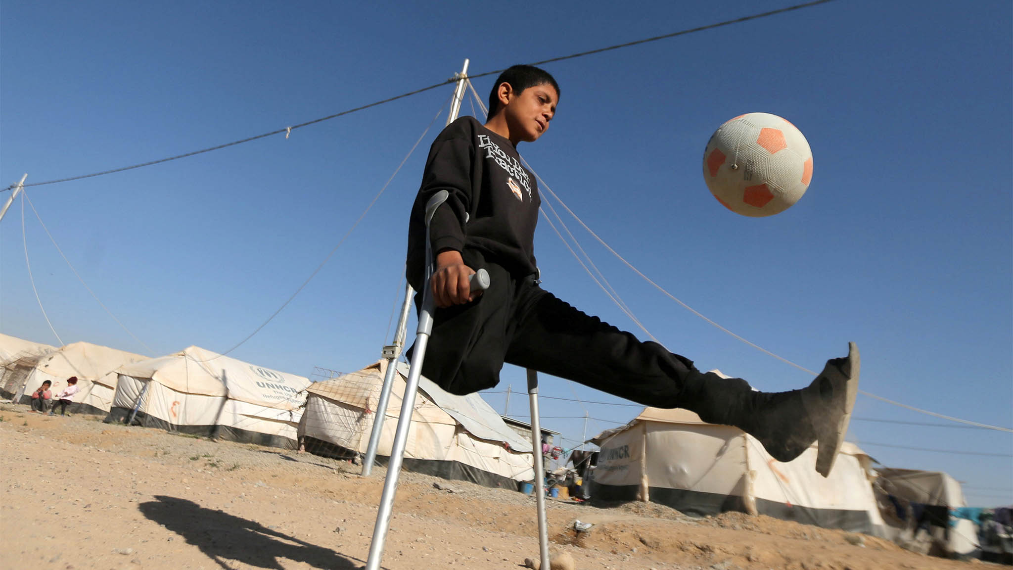 Jasim plays football in Debaga camp, on the outskirts of Erbil