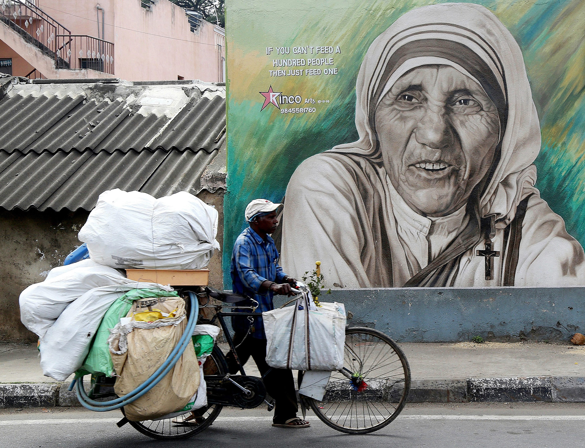 An Indian cyclist passes a mural depicting Catholic nun Mother Teresa, in Bangalore, India, 17 November 2016. Mother Teresa was born Agnes Gonxha Bojaxhiu on 26 August 1910 to Albanian parents in Skopje, Macedonia (FYROM) and died on 05 September 1997 in Calcutta, India. She began her missionary work with the poor in Calcutta in 1948, and won the Nobel Peace Prize in 1979. Following her death in 1997 she was beatified by Pope John Paul II and given the title Blessed Teresa of Calcutta.  EPA/JAGADEESH NV  EPA/JAGADEESH NV