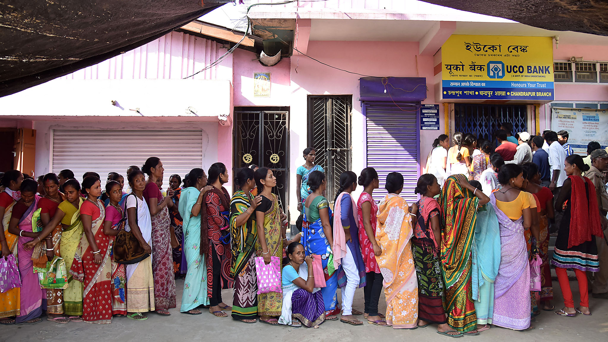 Indian villagers wait in a queue outside a bank to deposit and exchange 500 and 1000 rupee notes in Chandrapur Village, some 30 kms from Guwahati on November 15, 2016.  / AFP / Biju BORO        (Photo credit should read BIJU BORO/AFP/Getty Images) *** BEST