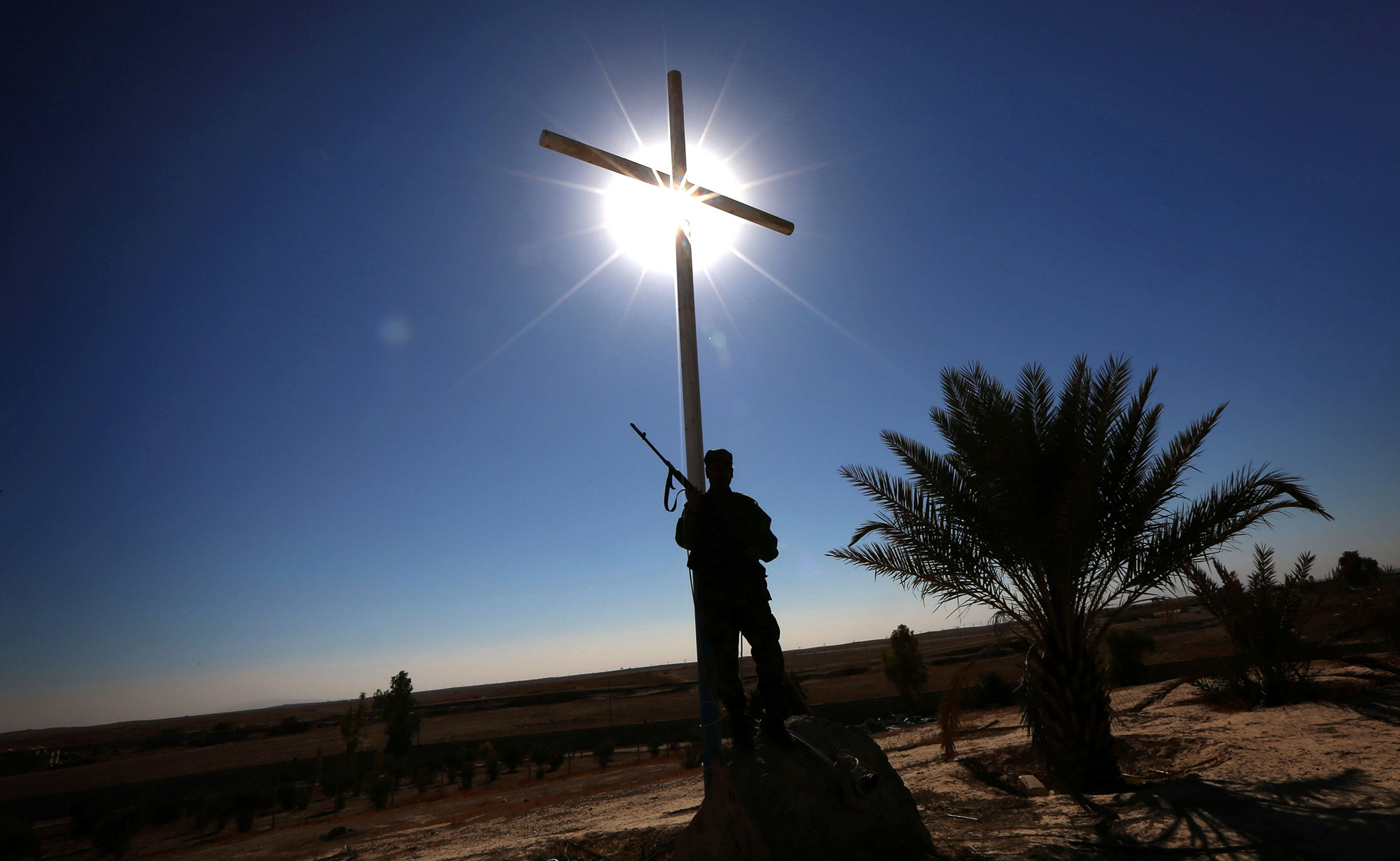 A member of the Iraqi Christian forces Kataeb Babylon (Babylon Brigades) stands guard beneath a cross at the Mar Benham Syriac Catholic monastery in the town of Khidr Ilyas, southeast of Mosul, on November 22, 2016. Iraqi fighters battling to oust the Islamic State group from Mosul captured the Catholic Mar Benham monastery on November 20, allowing its priests to return. Dating back to the fourth century AD, the monastery lies just 30 kilometres south of Iraq's second city which became a bastion of the jihadist group which swept across northern Iraq in 2014. / AFP PHOTO / SAFIN HAMEDSAFIN HAMED/AFP/Getty Images