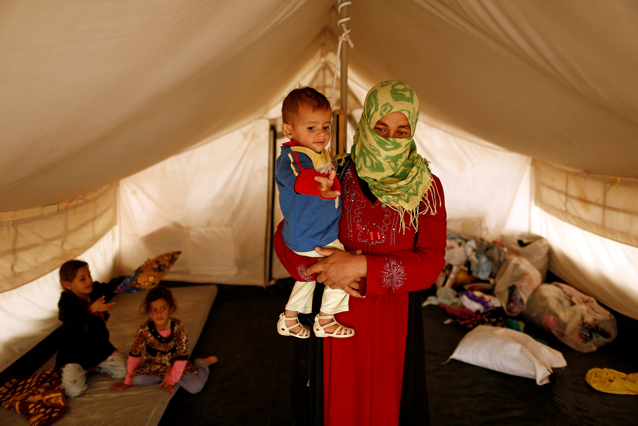 "A woman who fled from Mosul carries her son Riyad, 1, who was born under Islamic State rule and has no identity documents recognised by Iraqi authorities, in Debaga refugee camp, Iraq November 10, 2016. REUTERS/Zohra Bensemra SEARCH ""CALIPHATE CHILDREN"" FOR THIS STORY. SEARCH ""WIDER IMAGE"" FOR ALL STORIES.?"