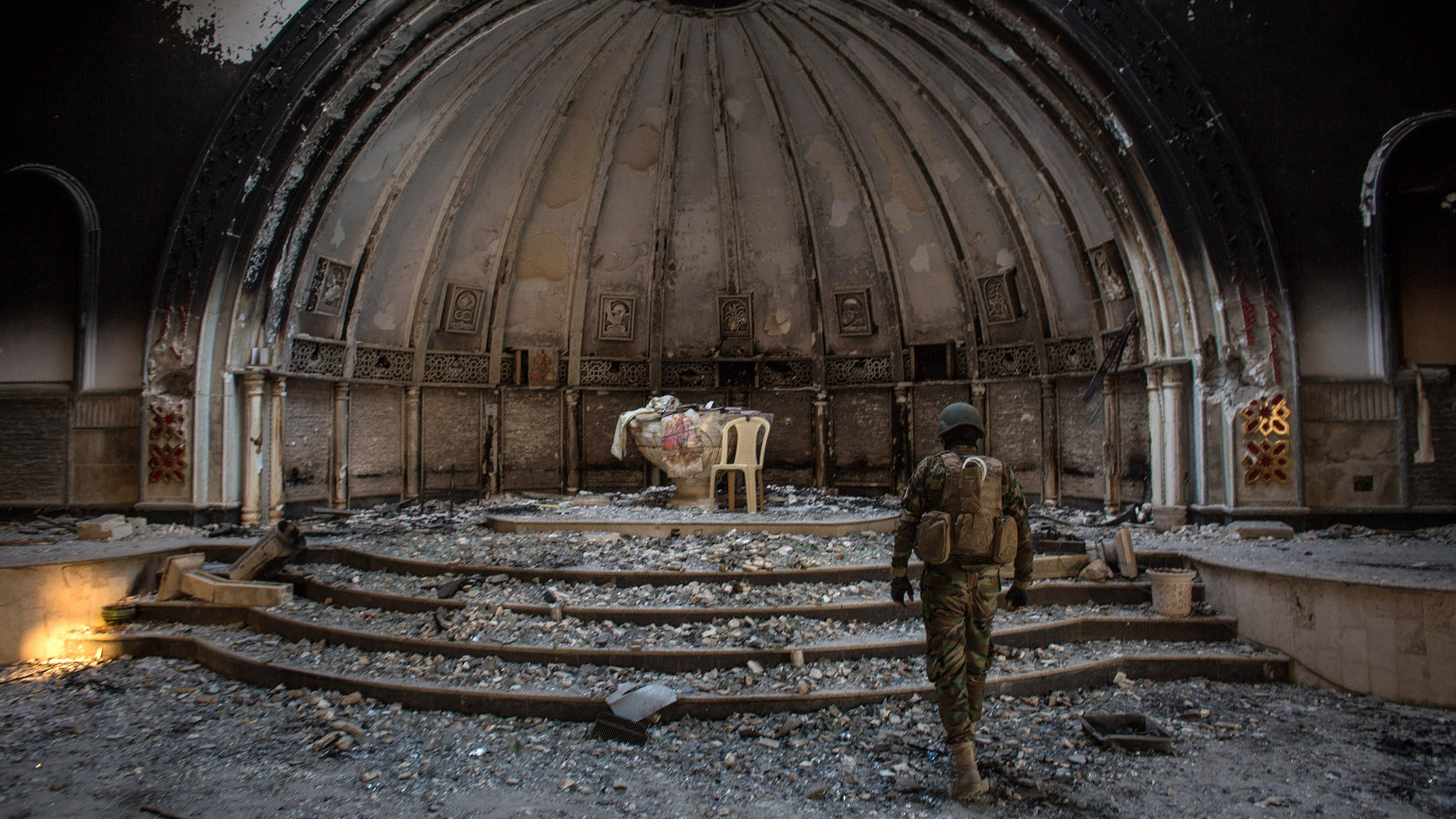A fighter from the NPU (Nineveh Plain Protection Units) waks through a destroyed church on November 8, 2016 in Qaraqosh, Iraq. The NPU is a military organization made up of Assyrian Christians and was formed in late 2014 to defend against ISIL. Qaraqosh, a largely Assyrian City just 32km southeast of Mosul was taken by ISIL in August, 2014 forcing all residents to flee, the town was largely destroyed with all of the churches burned or heavily damaged. The town stayed under ISIL control last week when it was liberated during the Mosul Offensive.  (Photo by Chris McGrath/Getty Images) ***BESTPIX***